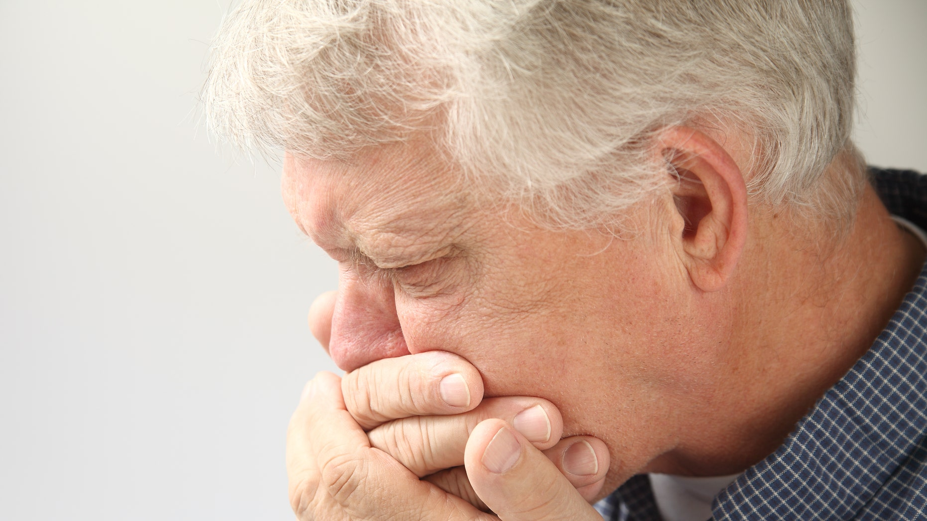 senior man holds his hand to his mouth while feeling nauseous