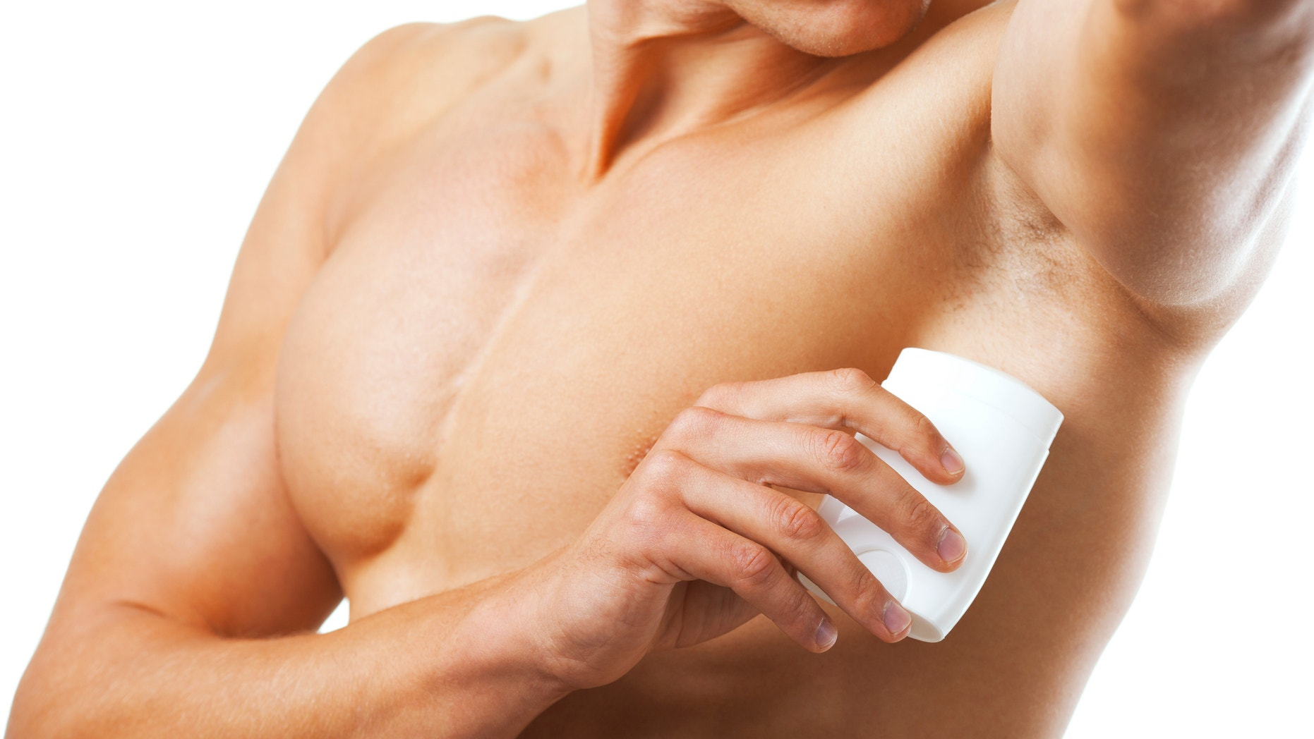 A man takes care of his hygiene by applying deodorant to his armpit.
