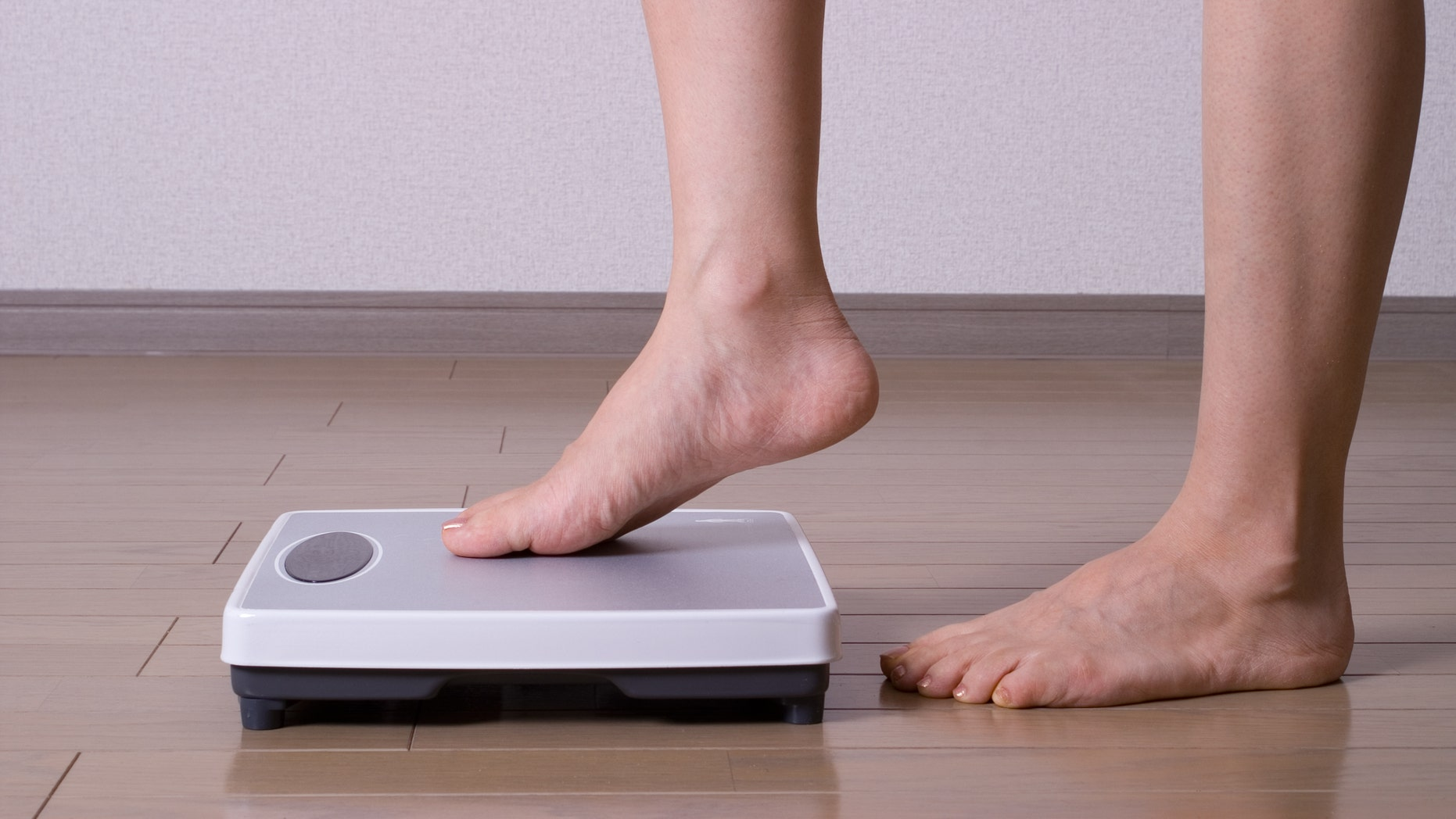 Woman stepping on scales and weighing herself