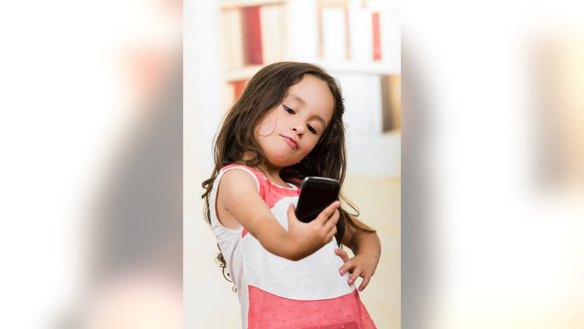 portrait of cute little happy using cell phone taking a selfie