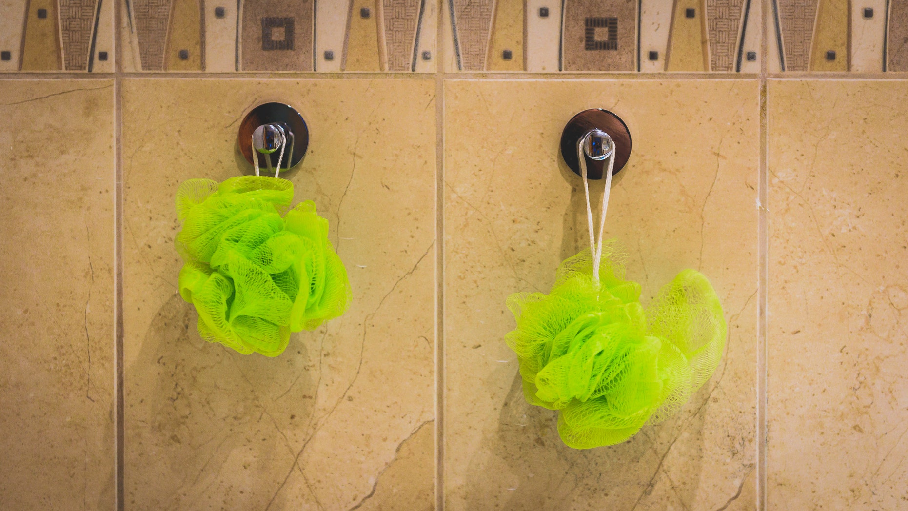 Two green bath sponges hanging from the bathroom wall. Bath accessories hanging from bathroom tiles.