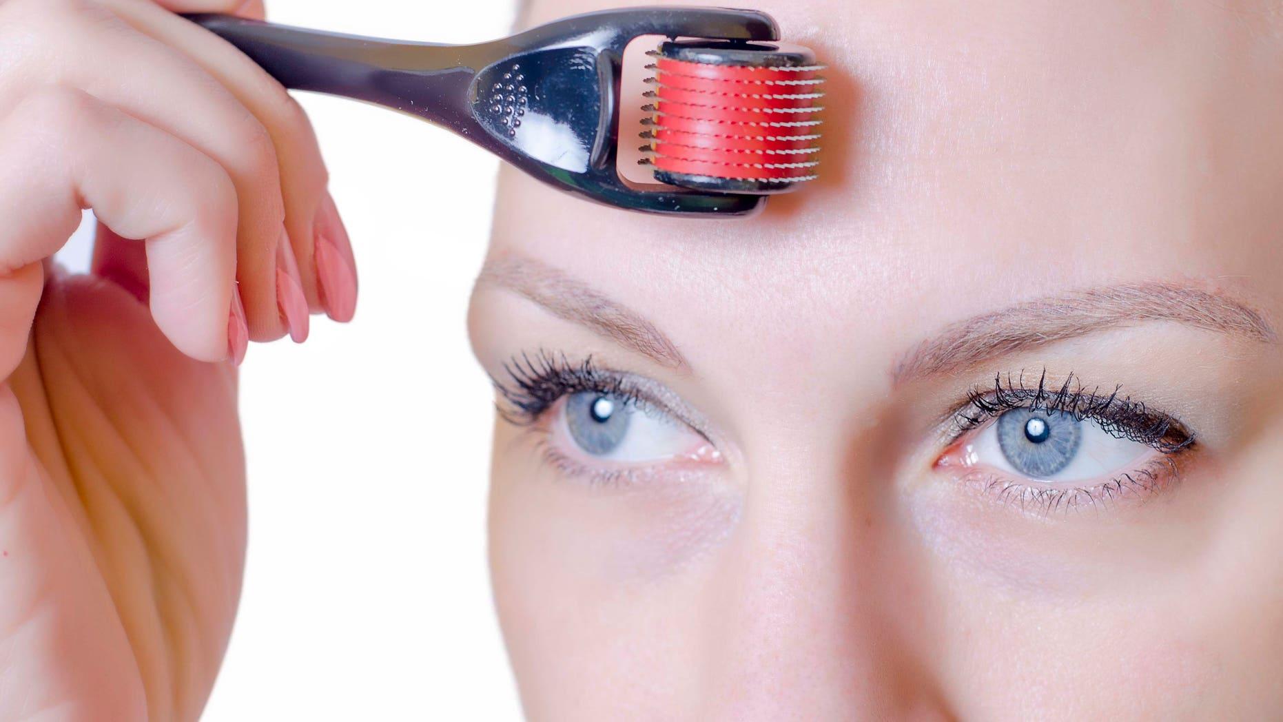 Medical cosmetic procedure. Mikronidling. Beautician performs Dermaroller procedure.