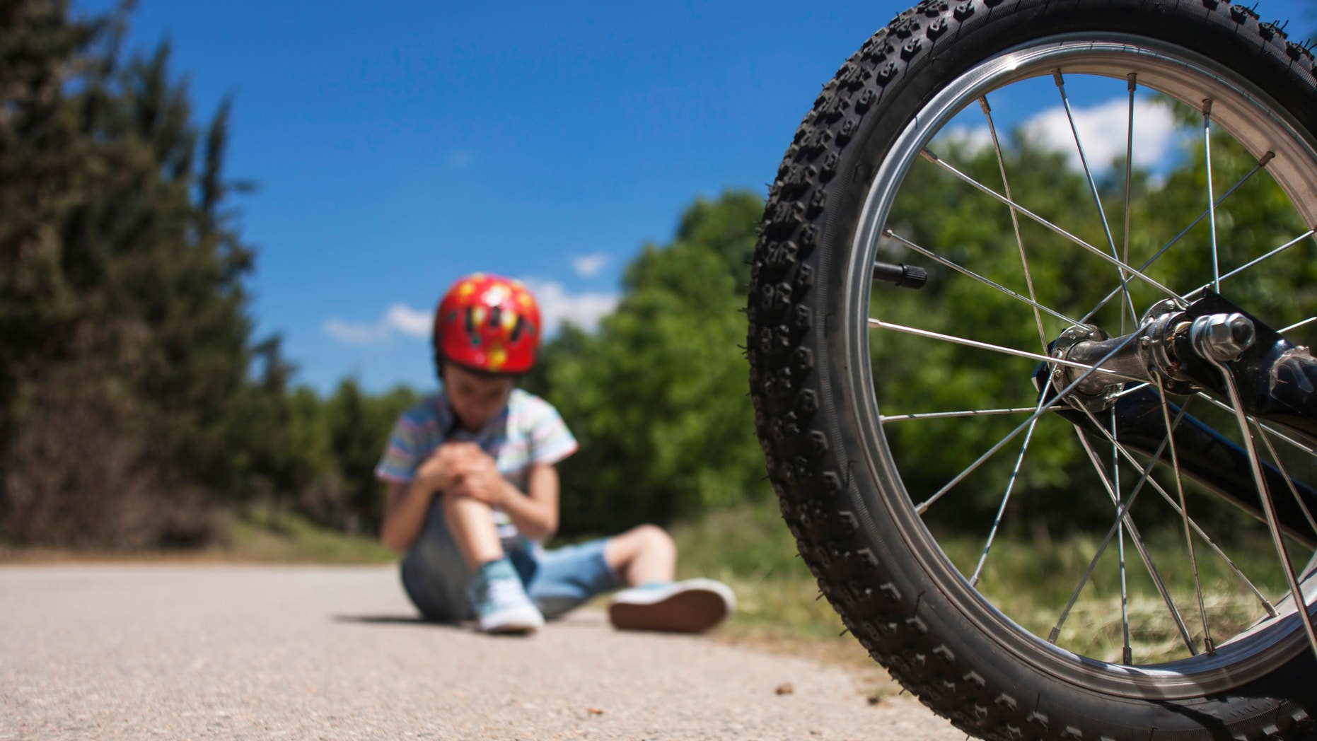 Boy is lying hurt after a bicycle accident. Kids safety concept
