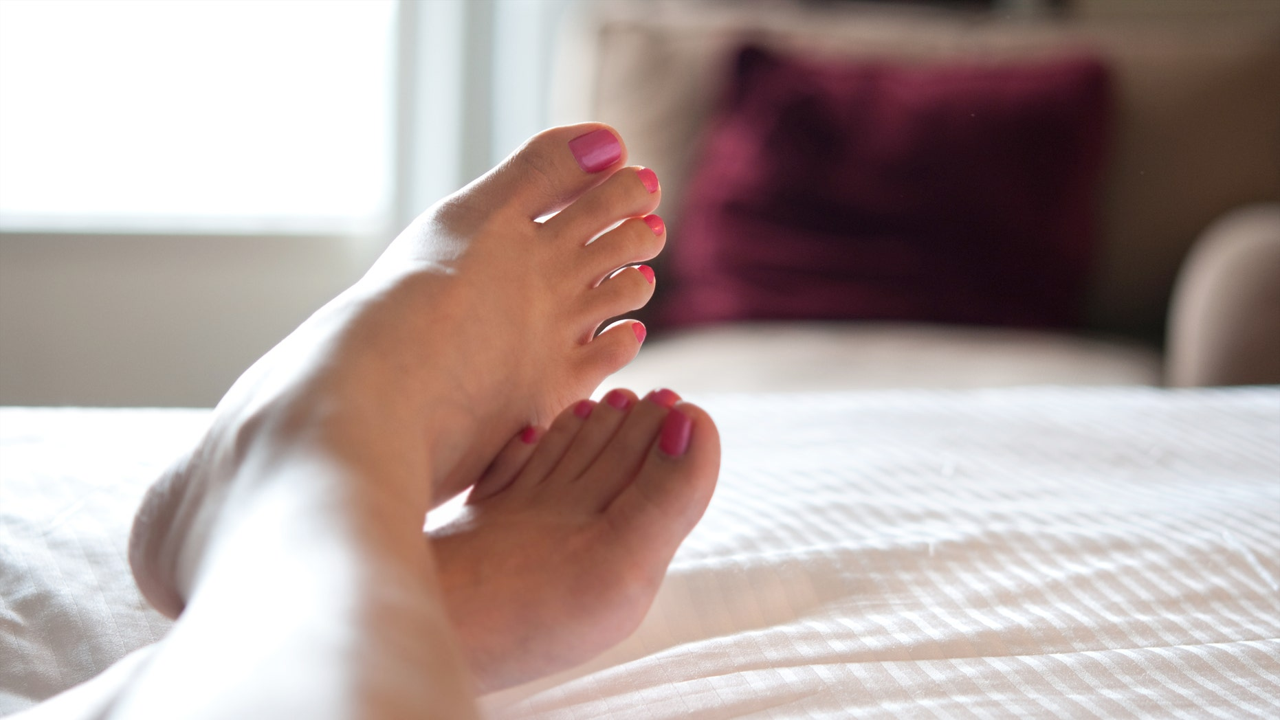 """""""Close up of a woman's feet with pink pedicured toe nails. She's sitting on the bed with her legs crossed at the ankles, feeling rejuvenated, pampered and relaxed in a hotel room. Shallow depth of field.Related collections:"""""""