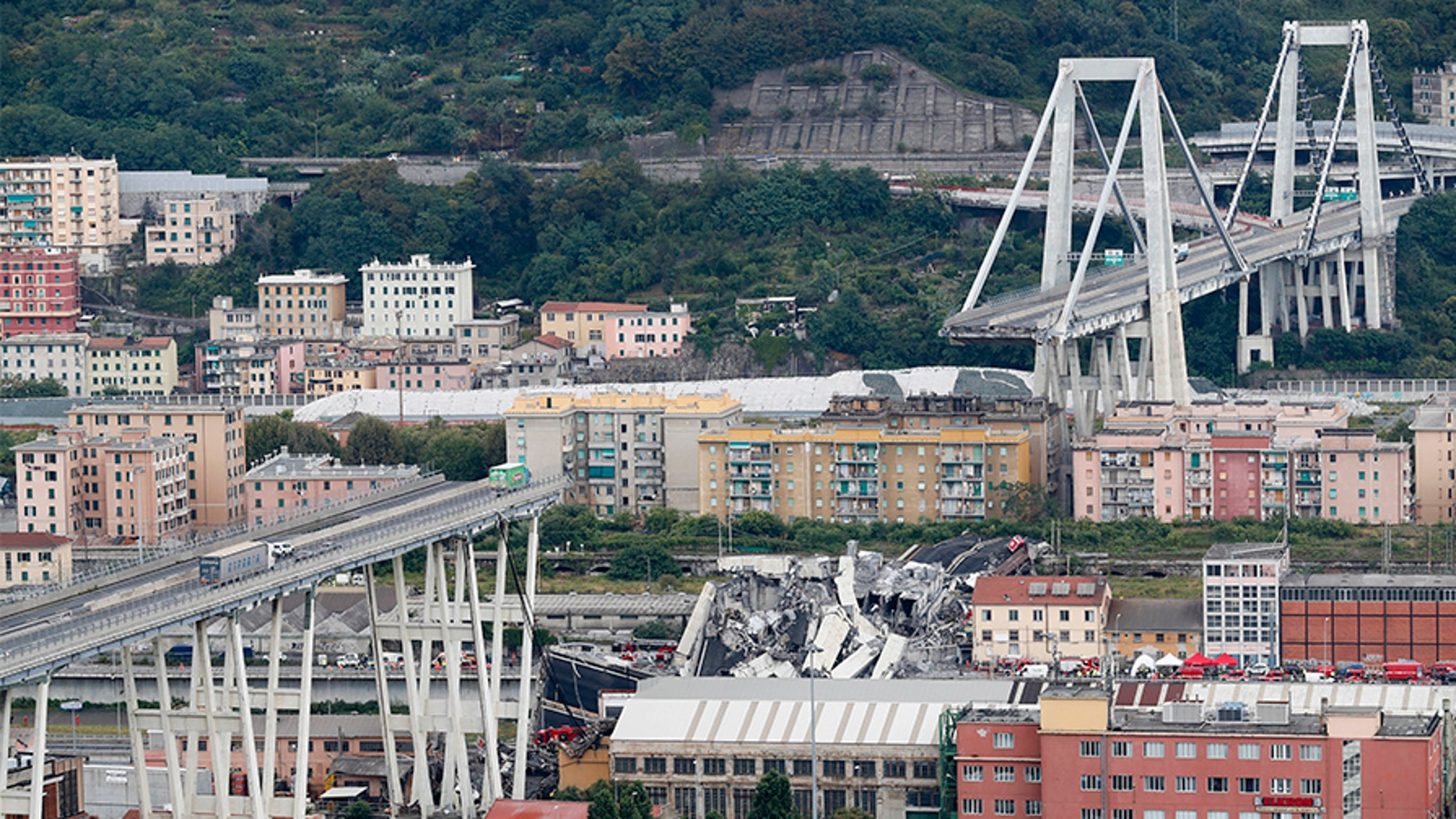 Cars are blocked on the Morandi highway bridge after a section of it collapsed, in Genoa, northern Italy, Tuesday, Aug. 14, 2018. A large section of the bridge collapsed over an industrial area in the Italian city of Genova during a sudden and violent storm, leaving vehicles crushed in rubble below. (AP Photo/Antonio Calanni)