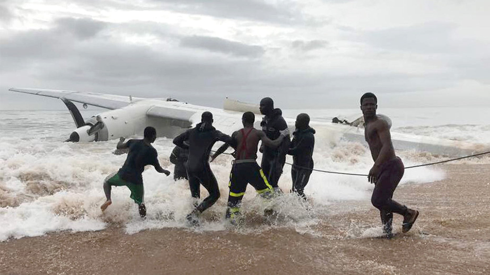 People pull the wreckage of a propeller-engine cargo plane after it crashed in the sea near the international airport in Ivory Coast's main city, Abidjan, October 14, 2017. REUTERS/Ange Aboa - RC197222A600