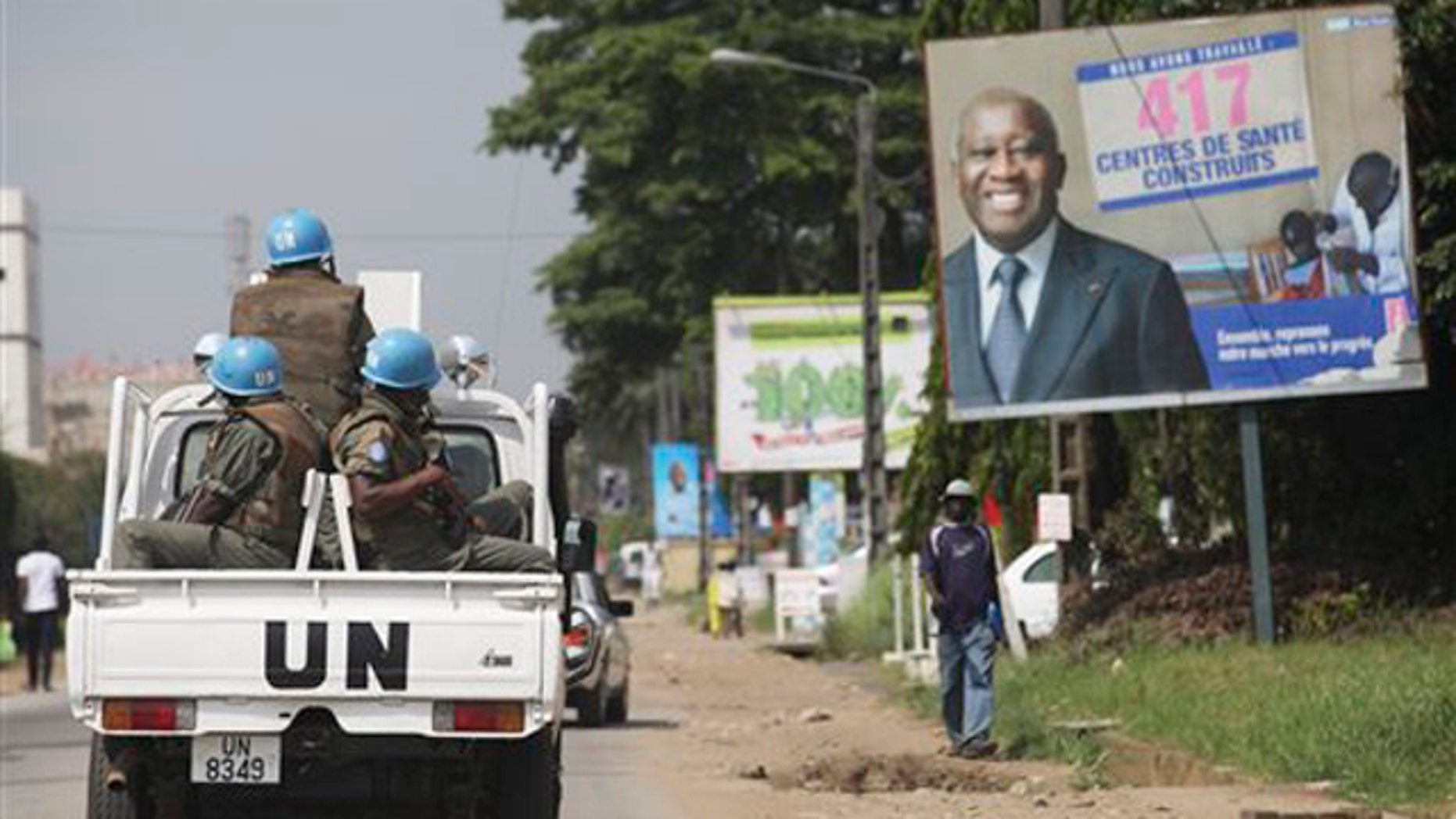 Dec. 23, 2010: U.N. forces drive past a billboard for President Laurent Gbagbo in Ivory Coast, Abidjan. The United Nations said Thursday that at least 173 people have been killed and dozens of others have gone missing or been tortured following Ivory Coast's disputed presidential election, which has prompted fears of a return to civil war.