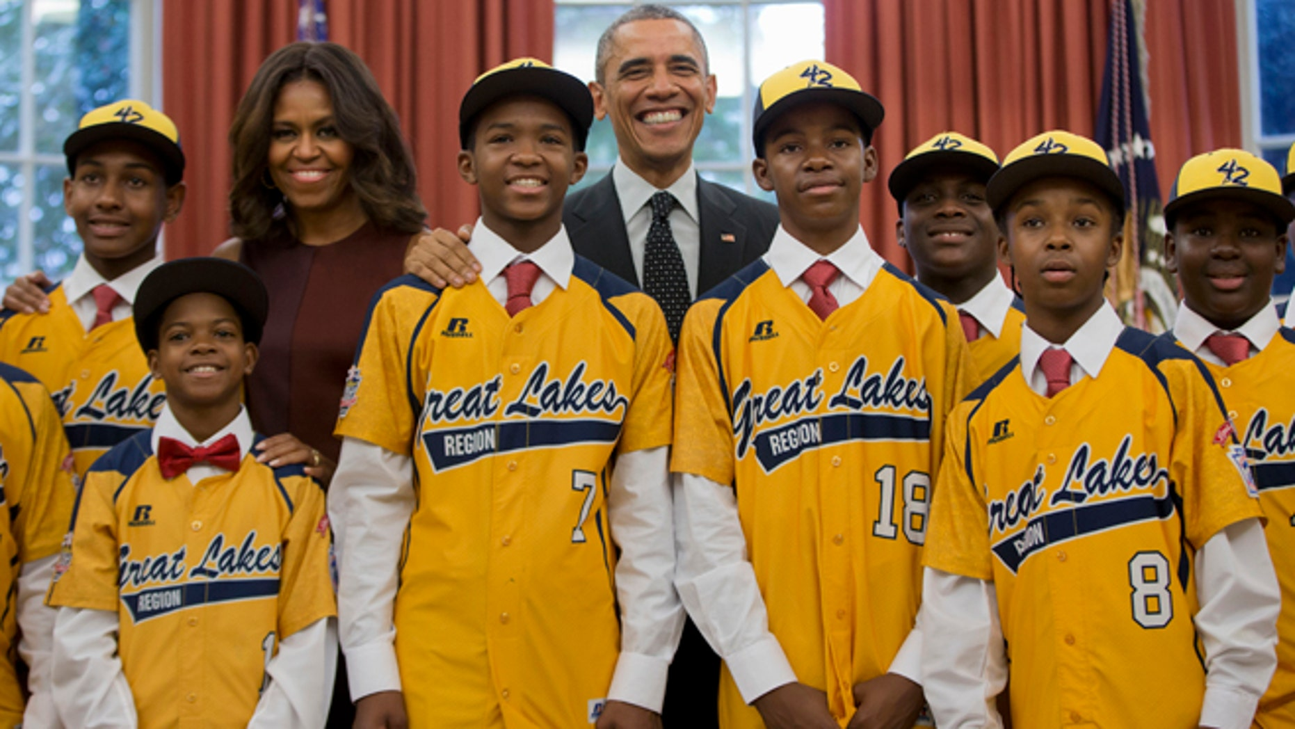 In this Nov. 6, 2014, file photo President Barack Obama and first lady Michelle Obama pose with members of the Jackie Robinson West little league team in the Oval Office of the White House in Washington. Little League International has stripped Chicago's Jackie Robinson West team of its national title after finding the team falsified its boundary map.