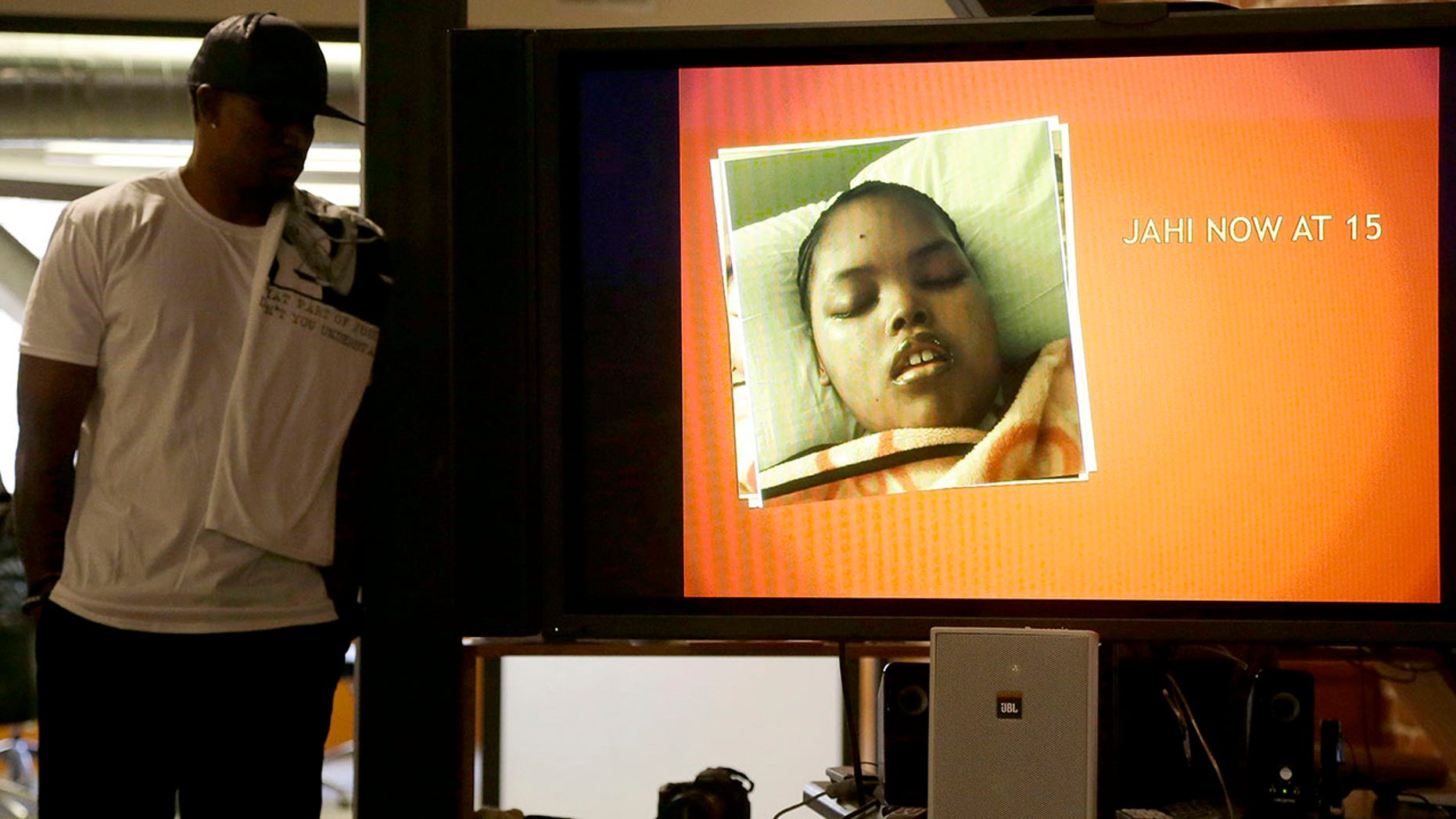 Dec. 23, 2015: In this file photo, a photo of Jahi McMath is shown on a video screen next to her uncle Timothy Whisenton at a news conference in San Francisco.