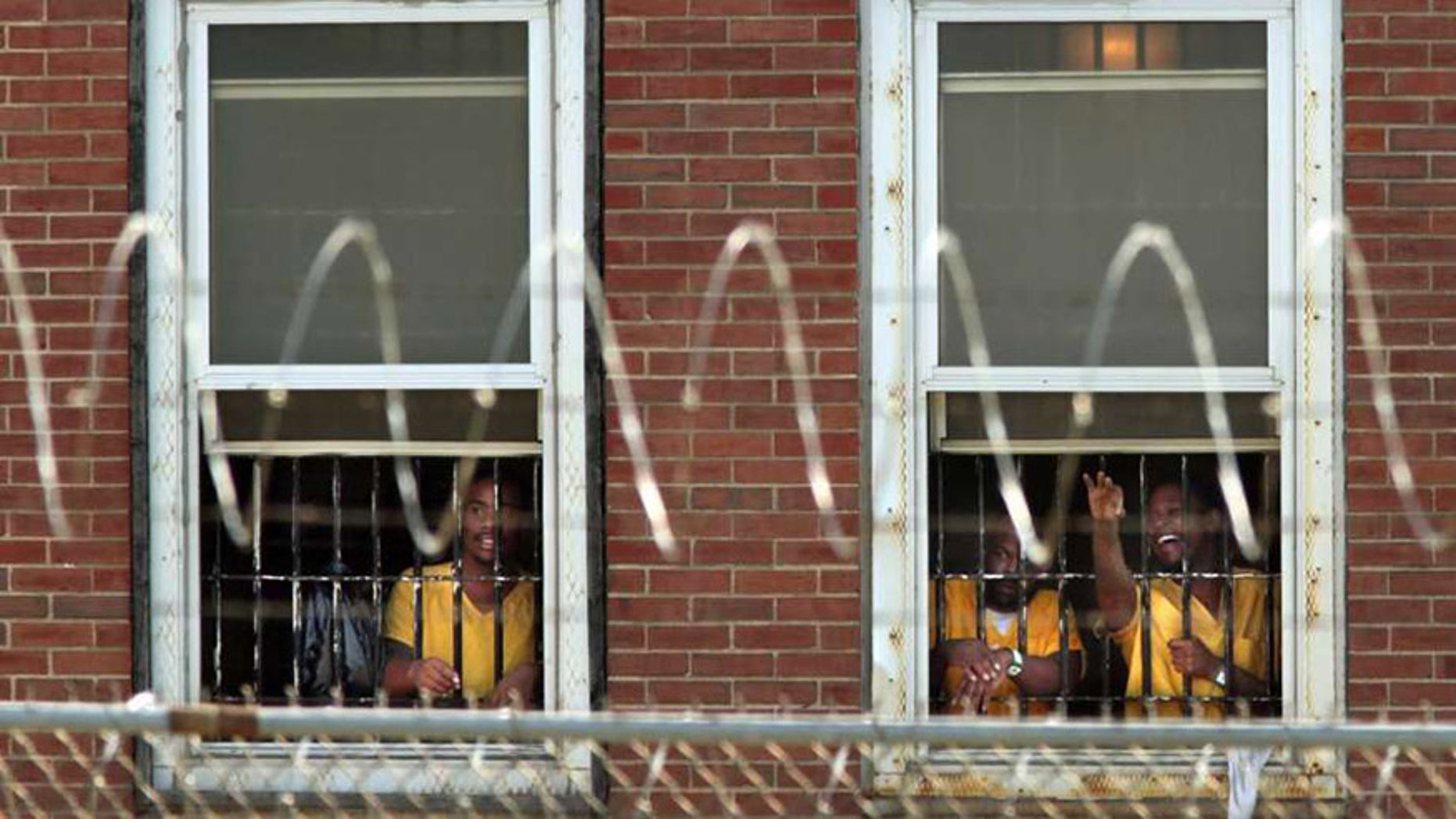 Inmates watch the arrival of temporary air conditioning units at the St. Louis Medium Security Institution.