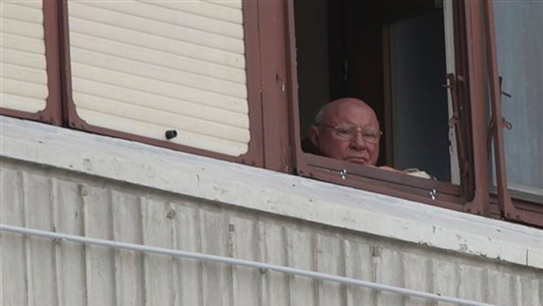 In this July 28, 2014, photo, Jakob Denzinger looks from his apartment window in Osijek, eastern Croatia. The suspected former Nazi prison guard at Auschwitz and other death camps, Jakob Denzinger, has died in his native Croatia at the age of 92.  (AP Photo/Darko Bandic)