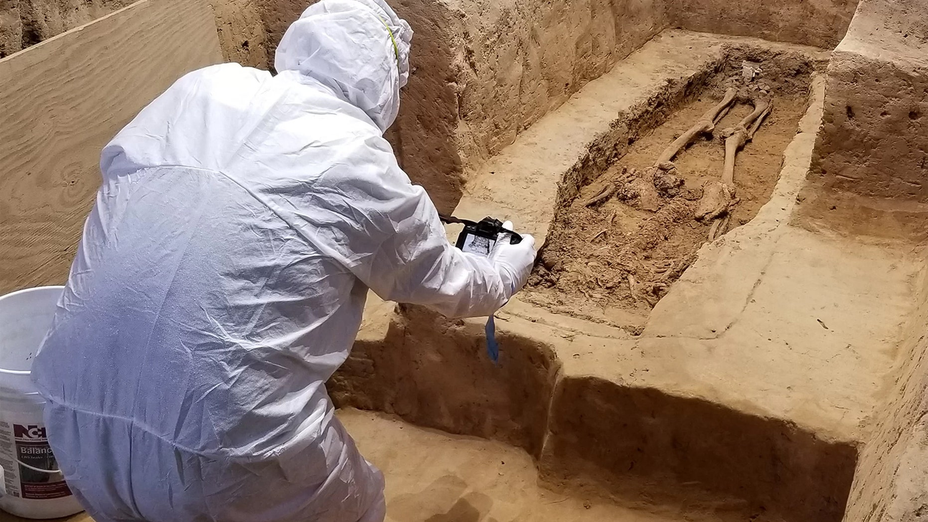An archaeologist investigates the burial while wearing a suit that will minimize contamination to the historical site. Credit: Jamestown Rediscovery