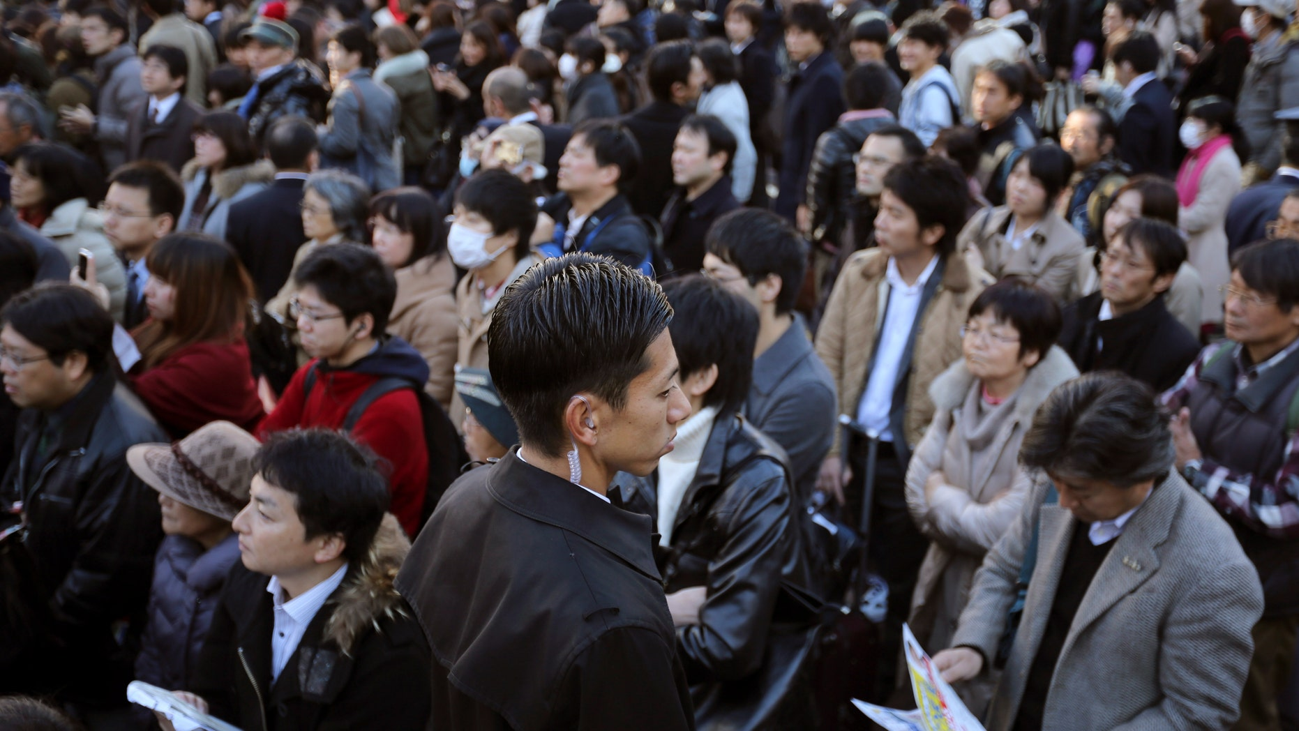 Dec. 13, 2014: A plainclothes police officer, center, stands guard as supporters and passersby listen to a speech by Banri Kaieda