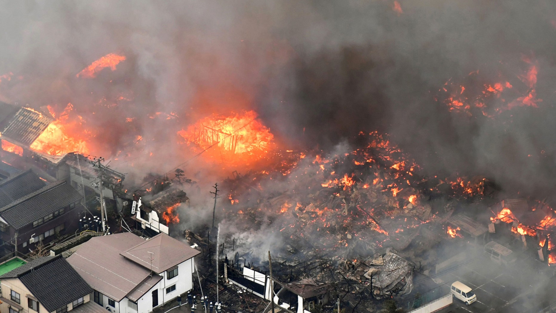 Smoke billow from houses during a fire in Itoigawa, northern Japan, Thursday, Dec. 22, 2016.