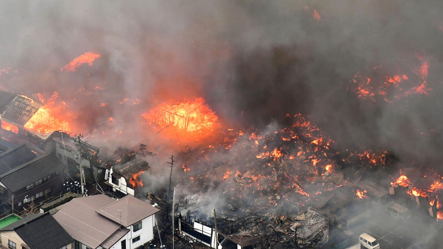 Smoke billow from houses during a fire in Itoigawa, northern Japan, Thursday, Dec. 22, 2016.  A fire whipped by high winds has spread to at least 140 buildings in a small Japanese city on the Japan Sea coast. The fire department says the blaze started at a restaurant in Itoigawa city Thursday morning. By mid-afternoon, 140 houses and other buildings had caught fire, and the fire is still spreading.  (Kyodo News via AP)