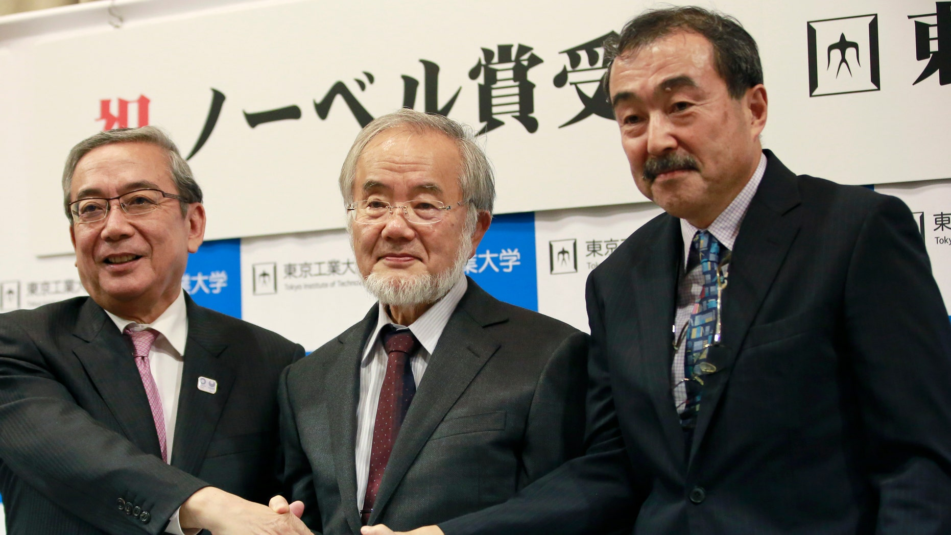 Nobel Prize winner Yoshinori Ohsumi, center, poses with Tokyo Institute of Technology President Yoshinao Mishima, left, and its Excutive Vice President Makoto Ando after a press conference at the Tokyo Institute of Technology in Tokyo Monday, Oct. 3, 2016. Ohsumi won the Nobel Prize in medicine on Monday for discoveries on how cells break down and recycle content, a garbage disposal system that scientists hope to harness in the fight against cancer, Alzheimer's and other diseases