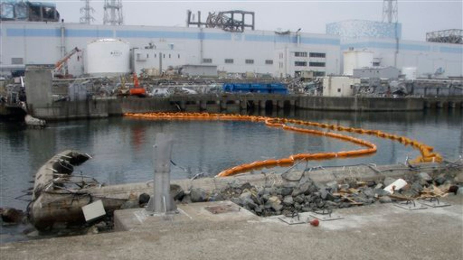 """This Sunday, April 10, 2011 photo released by Tokyo Electric Power Co. (TEPCO) shows orange colored floats suspending a """"silt fence"""" that was installed under water to help prevent contaminated water from spreading outside the Fukushima Dai-ichi nuclear power plant's bay. The tsunami-crippled nuclear complex is still leaking radiation after its cooling systems were knocked out by the March 11 tsunami (AP/TEPCO)"""