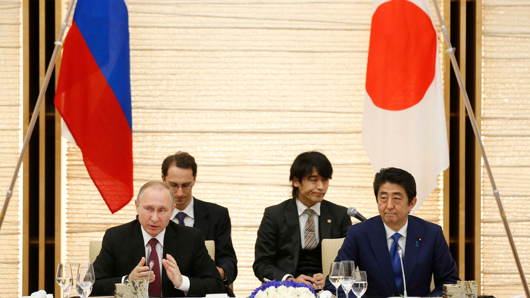 Russian President Vladimir Putin, left, and Japanese Prime Minister Shinzo Abe, right, attend a working lunch in Tokyo, Japan, Friday, Dec. 16, 2016.