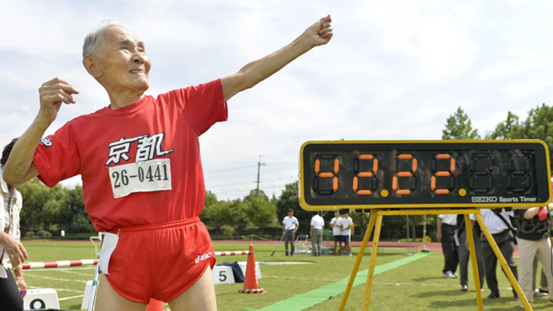 Sept. 23, 2015: Japan's Hidekichi Miyazaki, 105, poses like Jamaica's Usain Bolt in front of an electric board showing his 100-meter record time of 42.22 seconds at an athletic field in Kyoto, Japan.