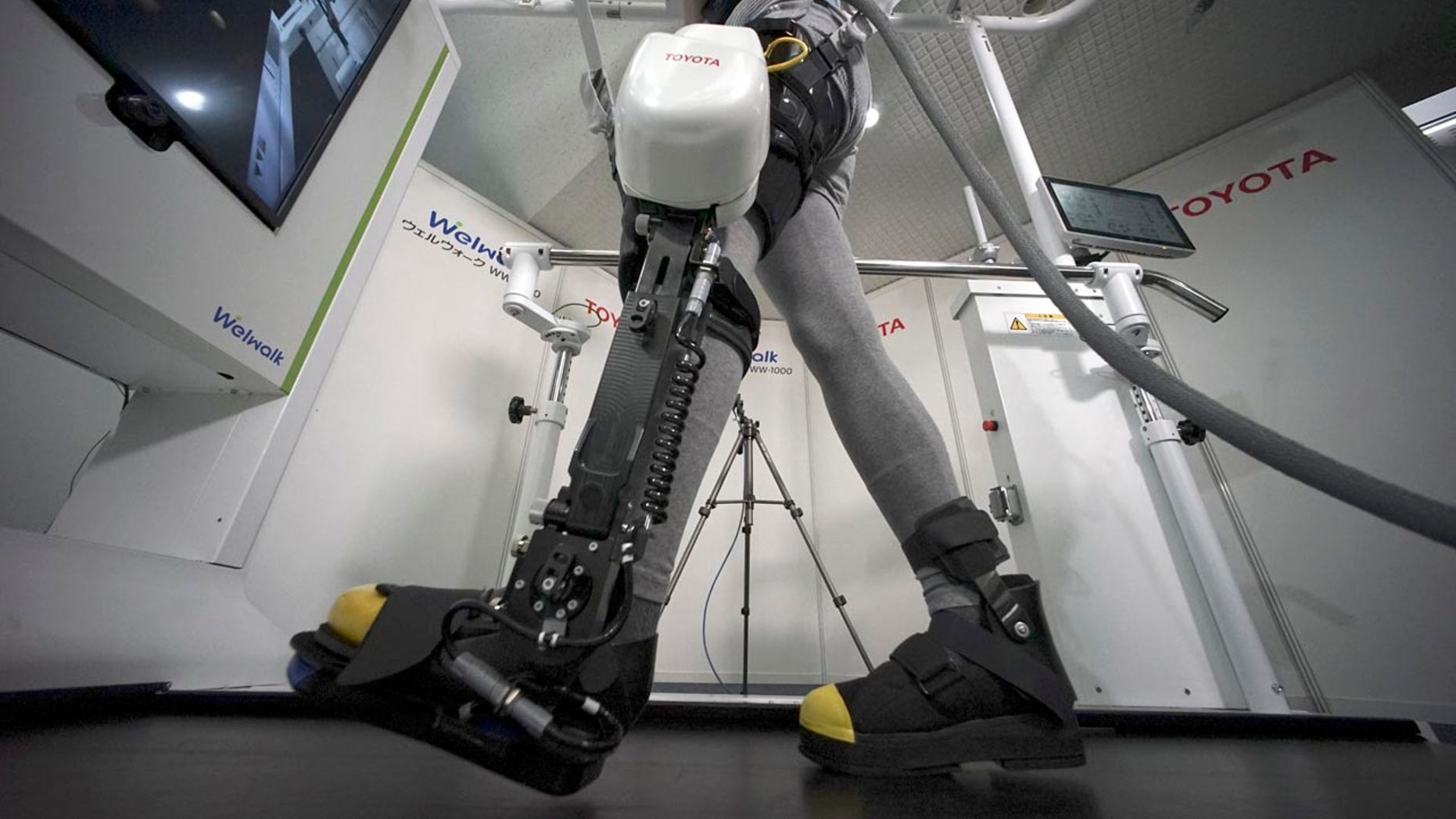 A model demonstrates the Welwalk WW-1000, a wearable robotic leg brace designed to help partially paralyzed people walk at the main system with treadmill and monitor, at Toyota Motor Corp.'s head office in Tokyo, Wednesday, April 12, 2017.