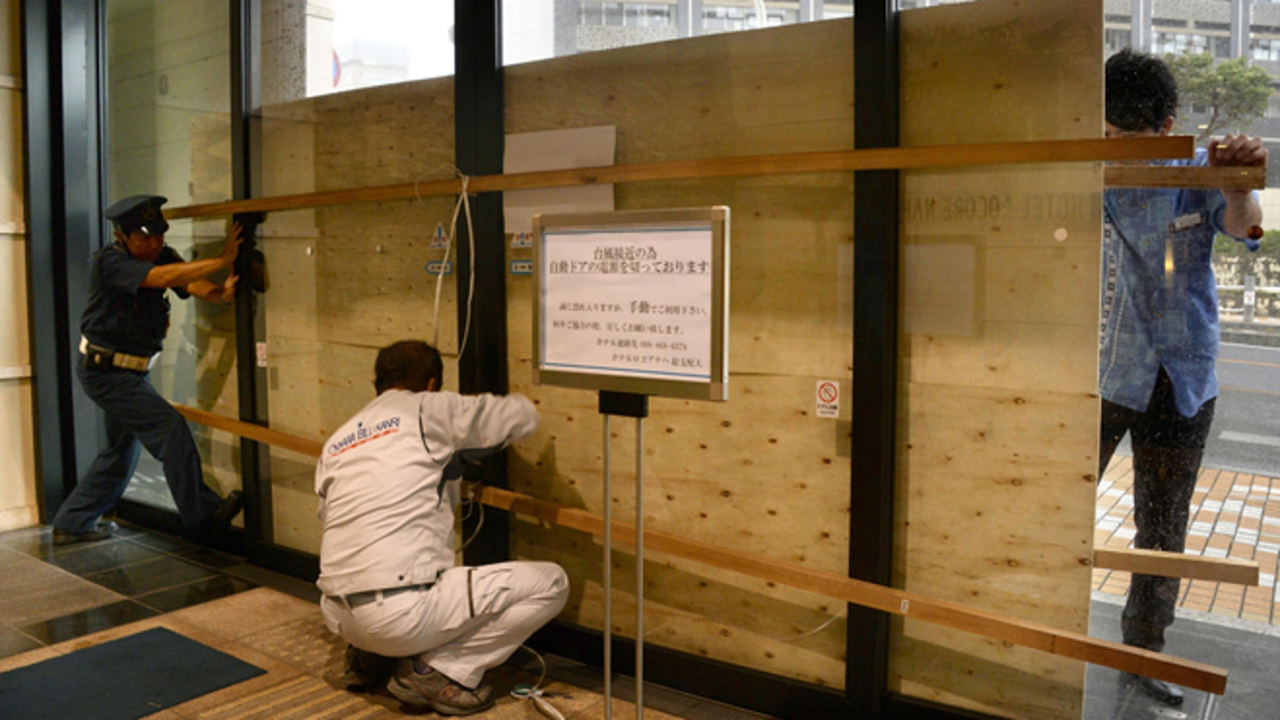 Oct. 11, 2014: Hotel employees and a guard secure its entrance door with a plywood board in preparation for approaching typhoon Vongfong in Naha, Okinawa.