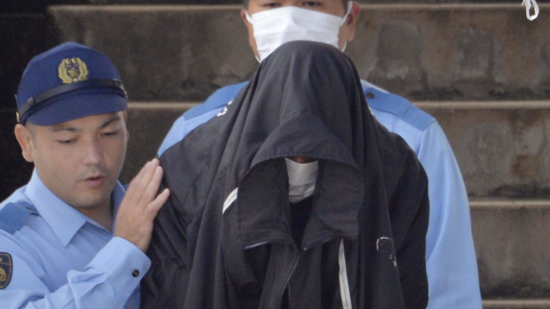 May 20, 2016: Police officers escort Kenneth Shinzato, center, an American working on a U.S. military base in Okinawa, out of Uruma Police Station to turn him over to the public prosecutor's office.