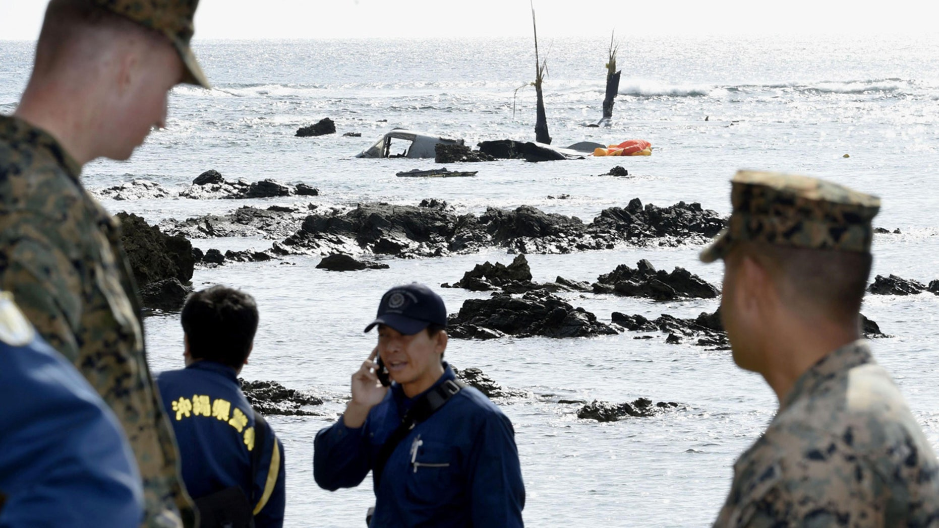 Officers of Okinawa Prefectural Police and the U.S. military investigate the site where debris of the MV-22 Osprey, background, was spotted in shallow waters off Okinawa.