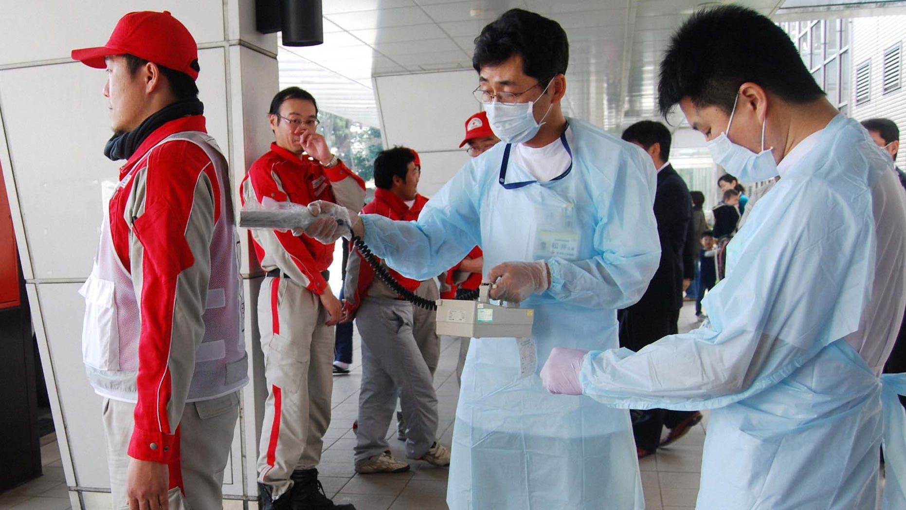 March 14: A Red Cross rescue worker, in red, is scanned for signs of radiation upon returning from Fukushima to his hospital in Nagahama, Shiga Prefecture.