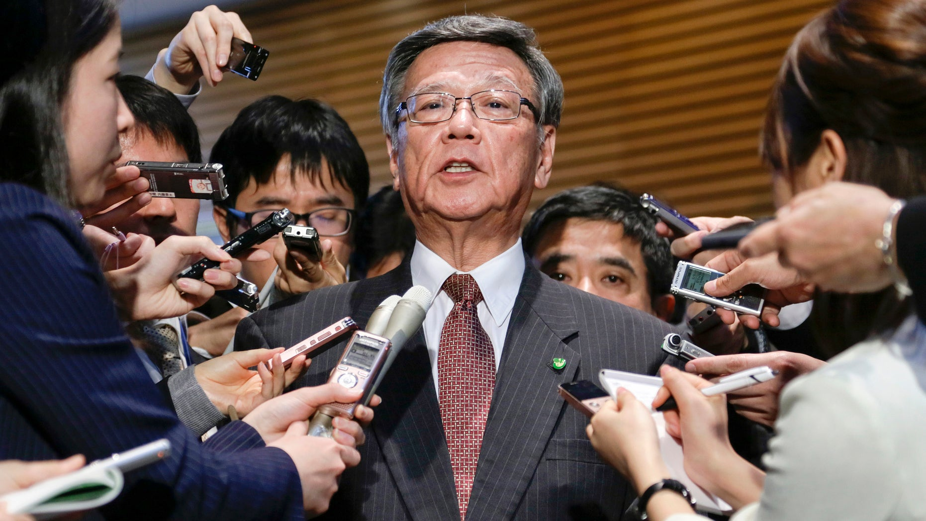 FILE - In this March 4, 2016 file photo, Okinawa Gov. Takeshi Onaga is surrounded by reporters after a meeting with Japanese Prime Minister Shinzo Abe at the latter's official residence in Tokyo.  Japan and the U.S. have marked a partial return of the land used by American troops to Okinawa in a ceremony on the southern island Thursday, Dec. 22, 2016, , but there was no sign the move was helping to lessen protests against the heavy U.S. military presence. Demanding an unconditional land return, Okinawa Gov. Onaga skipped Thursday's ceremony and joined a protest. (Kimimasa Mayama/Pool Photo via AP, File)