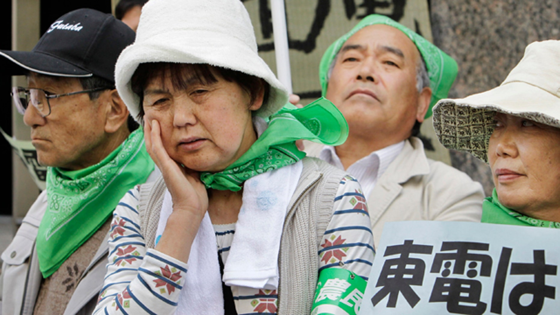 """April 26: Farmers, mostly from Fukushima Prefecture where the tsunami crippled Fukushima Dai-ichi plant is located, hold a protest in front of the Tokyo Electric Power Co. (TEPCO) headquarters in Tokyo Tuesday. More than 200 farmers affected by radiation spewing from the nuclear plant staged a demonstration to demand that TEPCO pays them adequate compensation for loss of income caused by having to leave their farms, or for having produced withdrawn from the market due to contamination fears. The placard at right reads: """"TEPCO, compensate!"""" (AP)"""