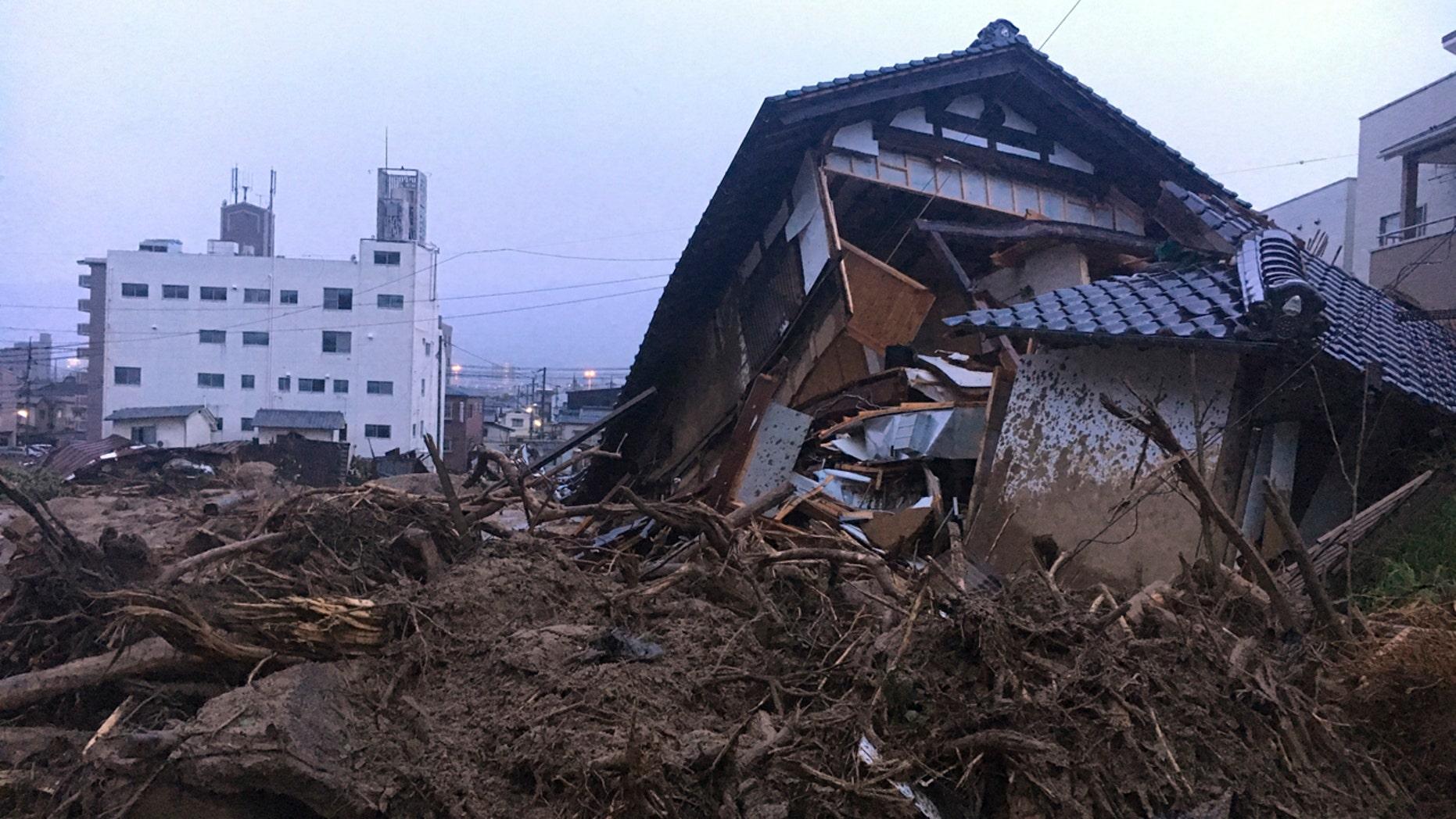Debris fills a small village following heavy rains Sunday, July 8, 2018, in Kuchita-Minami, Asakita-ku, Hiroshima, Japan. Searches continued Sunday night for dozens of victims still missing from the heavy rainfall that hammered southern Japan for the third straight day. (AP Photo Haruka Nuga)