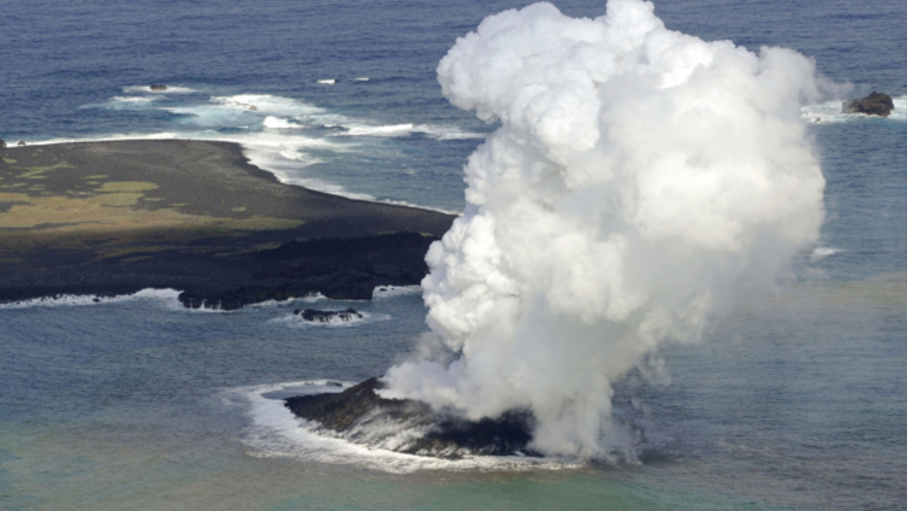 Nov. 21, 2013: Smoke billows from a new island off the coast of Nishinoshima, seen left above, a small, uninhabited island in the Ogasawara chain, far south of Tokyo.