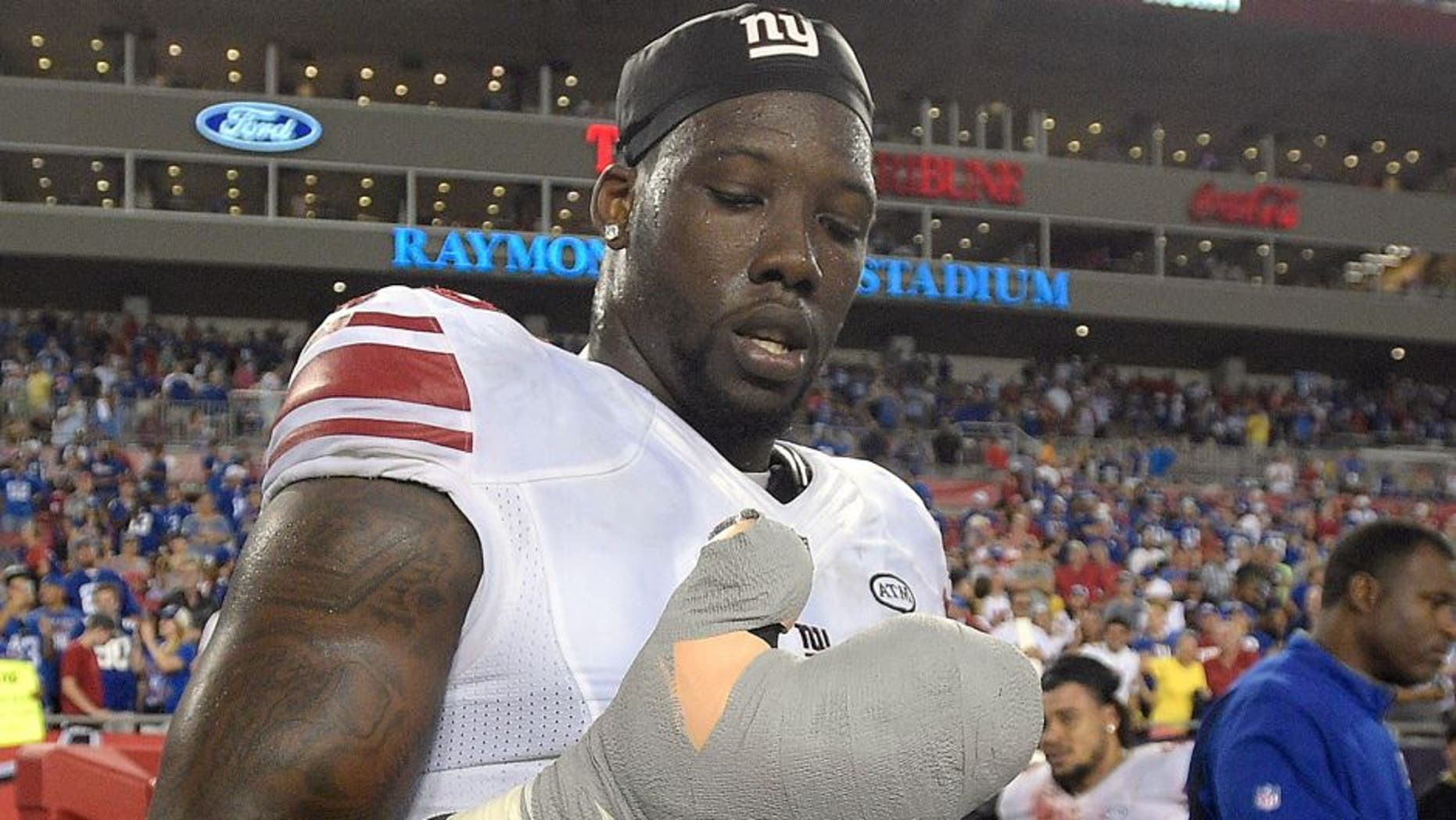 New York Giants defensive end Jason Pierre-Paul removes the bandage from his damaged hand after the Giants defeated the Tampa Bay Buccaneers 32-18 during an NFL football game Sunday, Nov. 8, 2015, in Tampa, Fla. (AP Photo/Phelan M. Ebenhack)