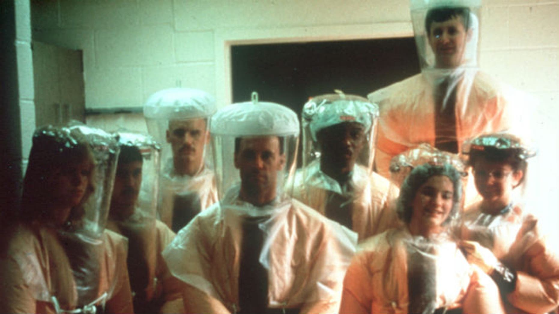 This handout photo provided by Dr. Jerry Jaax, taken in Dec. 1989, shows the Veterinary Medicine Division team from US Army Medical Research Institute of Infectious Diseases (USAMRIID) in the hot zone, Nonhuman primate quarantine facility in Reston, Va. As it turns out, Americans' introduction to the deadly Ebola virus 25 years ago came courtesy of an outbreak that turned out to be completely nonlethal to humans. (AP Photo/Gerald Jaax)