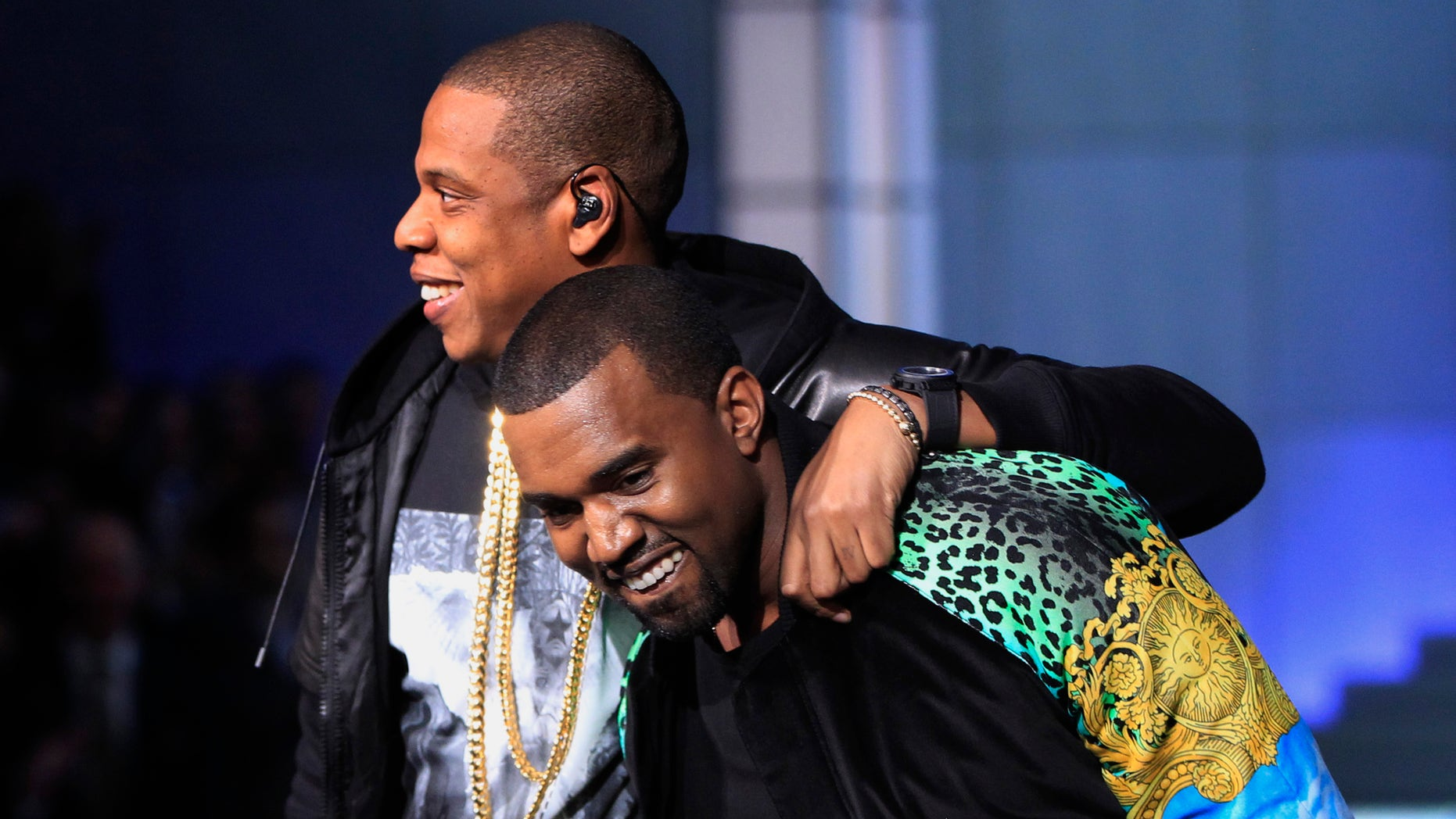 November 9, 2011. Rappers Jay-Z (L) puts his arm around Kanye West as they walk off stage after performing during the Victoria's Secret Fashion Show at the Lexington Armory in New York.