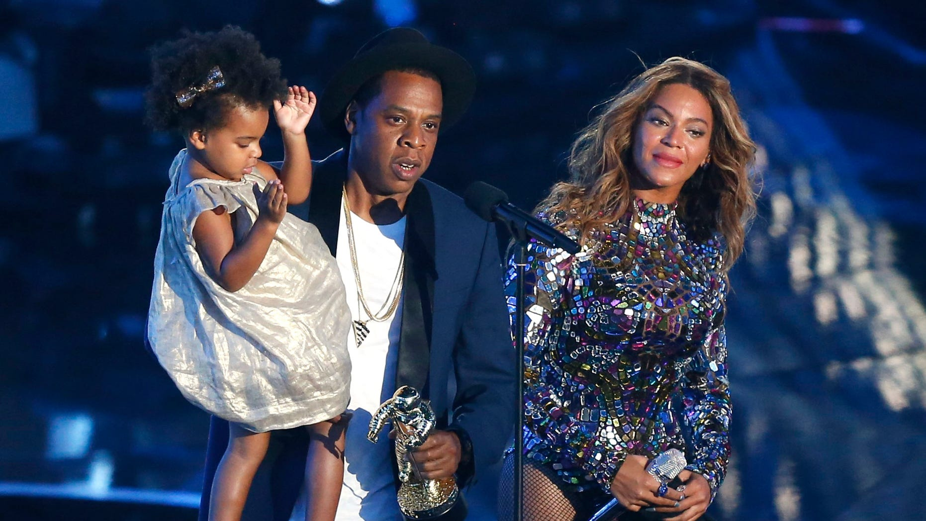 Jay-Z presents the Video Vanguard Award to Beyonce as he holds their daughter Blue Ivy during the 2014 MTV Video Music Awards in Inglewood, California August 24, 2014.  REUTERS/Mario Anzuoni (UNITED STATES - Tags: ENTERTAINMENT)(MTV-SHOW) - RTR43KSX