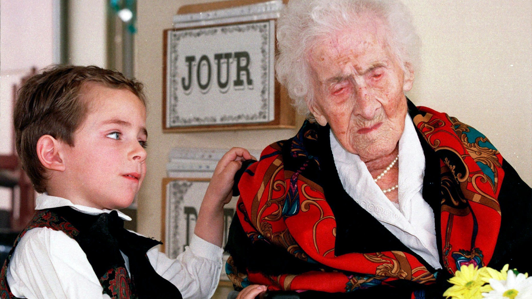 In this Feb. 12, 1997 file photo shows Thomas, 5, looks at Jeanne Calment after he brought her flowers at her retirement home in Arles, southern France. Calment, believed to be the world's oldest person, died at the age of 122 in 1997. New research published in the journal Nature on Wednesday, Oct. 5, 2016 suggests there's a limit to our life span and that the odds of breaking Calment's record are small.