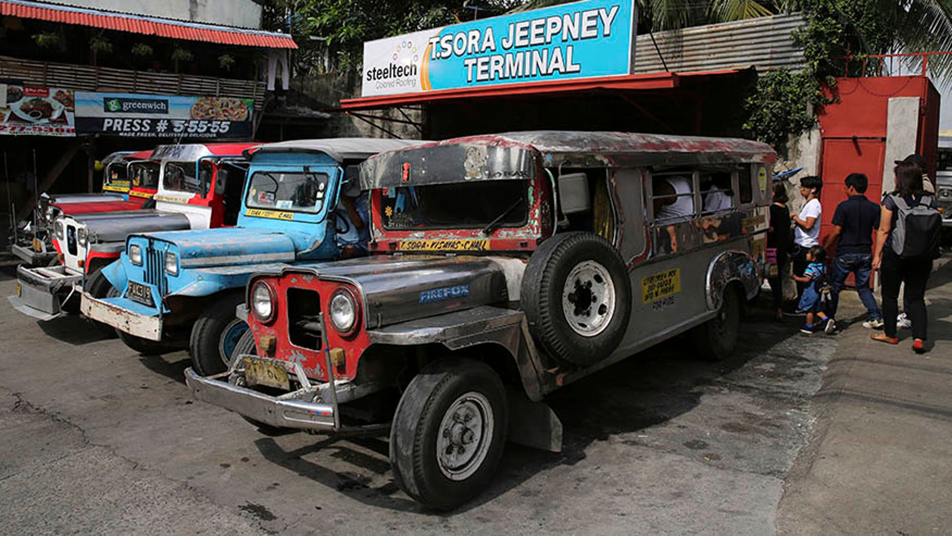 In this Sept. 26, 2017, photo, passengers board jeepneys at a terminal in Manila, Philippines. The iconic passenger jeepney is chugging toward change and uncertainty as a government modernization program aims to improve their engines, safety and convenience in an overhaul that poor Filipino drivers and owners say they can't afford. (AP Photo/Aaron Favila)