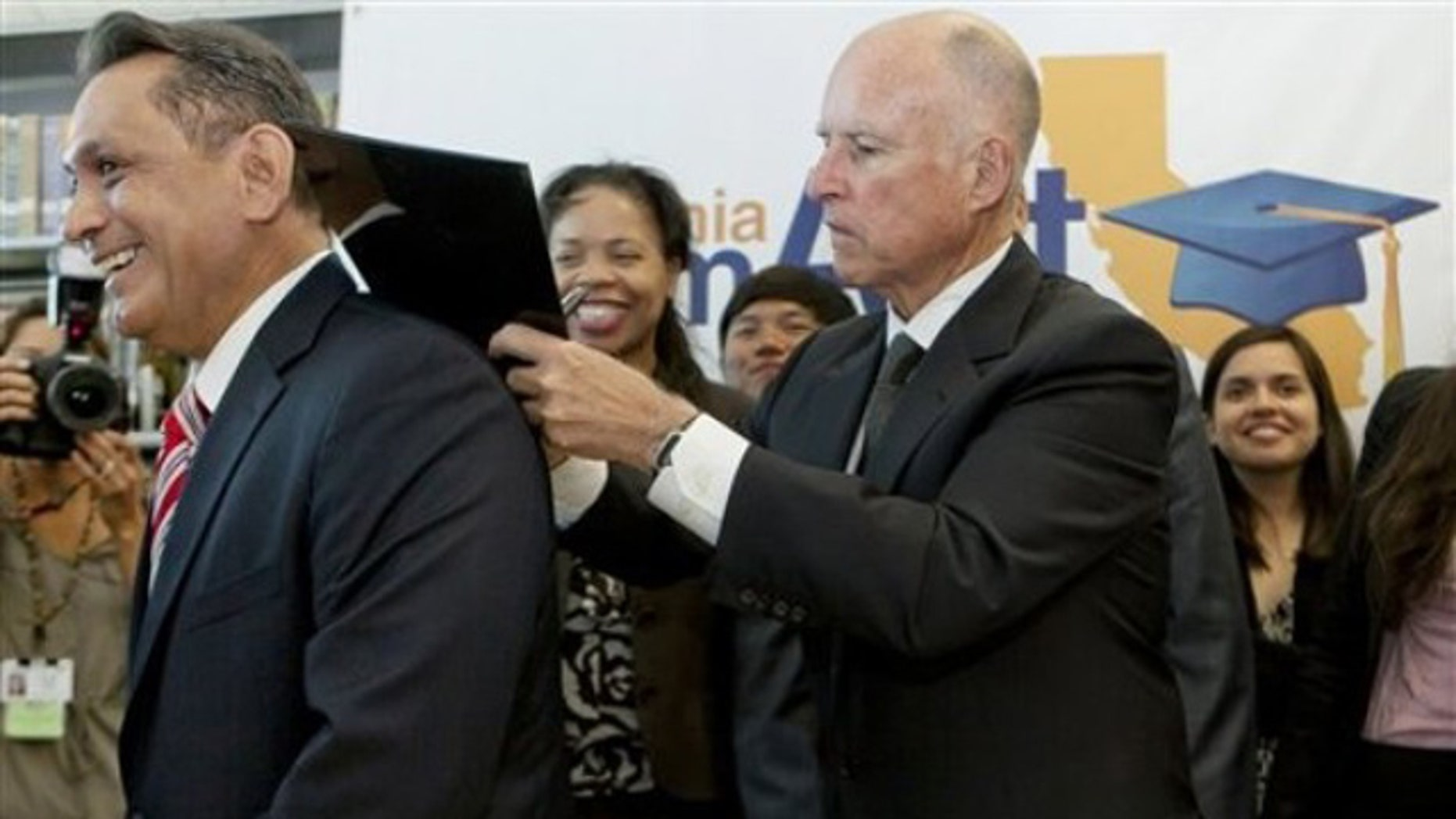 California Gov. Jerry Brown, right, signs AB 130 Dream Act bill on the back of Assemblyman Gil Cedillo, left, at the Mather Luther King Library at the Los Angeles City College Monday, July 25, 2011, in Los Angeles.