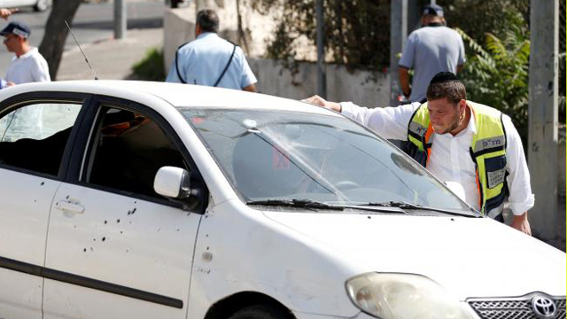 Oct. 9, 2016: An Israeli emergency worker looks into a car covered with bullet holes.