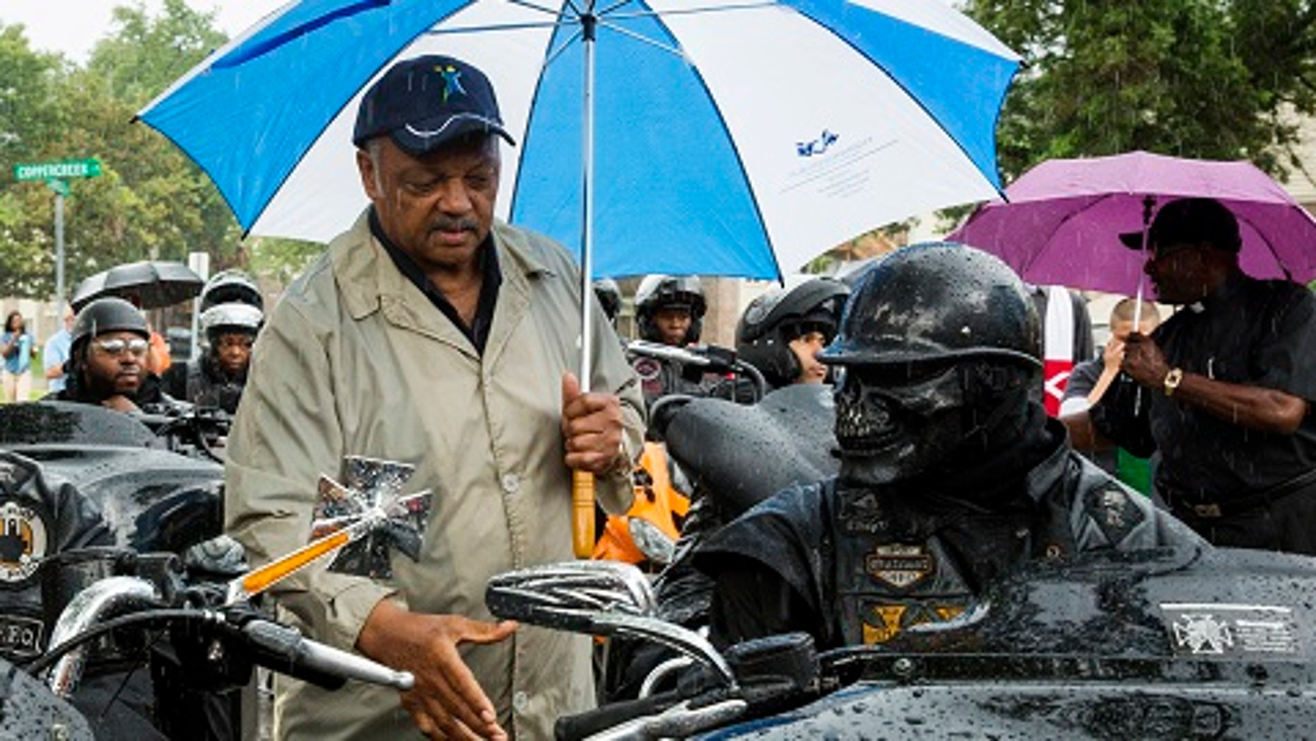 "Civil rights leader Jesse Jackson (C) greets members of the ""Outcast"" motorcycle club before a vigil in the neighborhood where teenager Michael Brown was shot, in Ferguson, Missouri, August 16, 2014. Tensions had temporarily cooled on Thursday night but by Friday evening, protesters were again swarming through a residential and retail district in the small town outside St. Louis that has become the site of repeated clashes between protestors and police forces. The unrest erupted after Ferguson police officer Darren Wilson, 28, shot and killed Brown shortly after noon last Saturday as Brown and a friend walked down a street that runs through an apartment complex where Brown's grandmother lives. REUTERS/Lucas Jackson (UNITED STATES - Tags: CIVIL UNREST CRIME LAW TPX IMAGES OF THE DAY) - RTR42O0M"