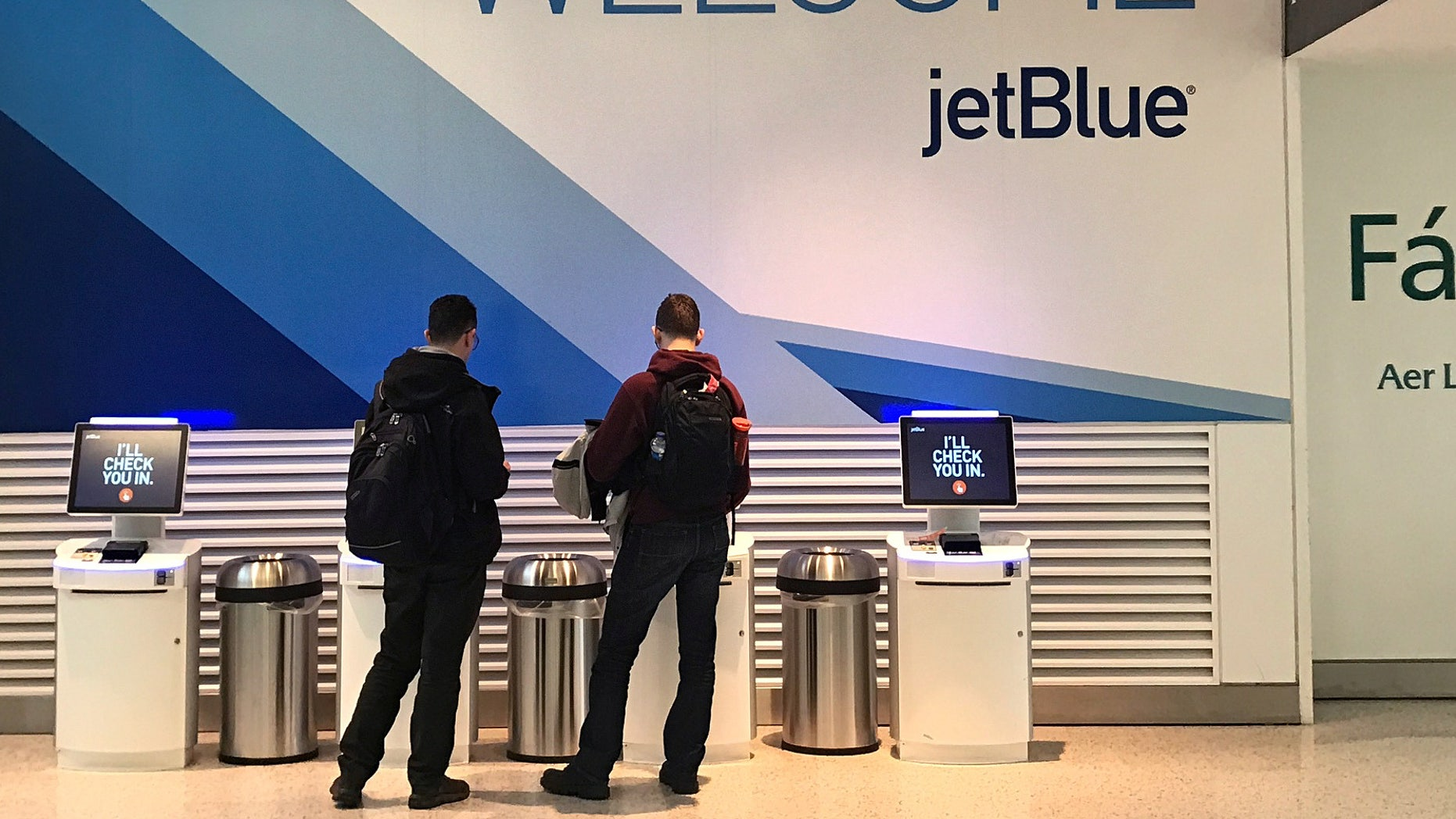 Travelers check-in at a JetBlue Airways kiosk at John F. Kennedy Airport in the Queens borough of New York, U.S., January 24, 2017.