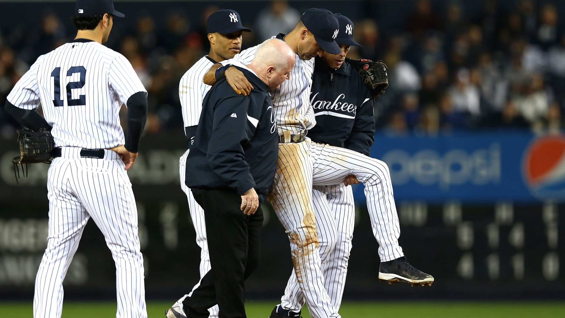 NEW YORK, NY - OCTOBER 13:  Derek Jeter #2 of the New York Yankees is carried off of the field by trainer Steve Donohue and manager Joe Girardi after Jeter injured his leg in the top of the 12th inning against the Detroit Tigers during Game One of the American League Championship Series at Yankee Stadium on October 13, 2012 in the Bronx borough of New York City, New York.  (Photo by Elsa/Getty Images)