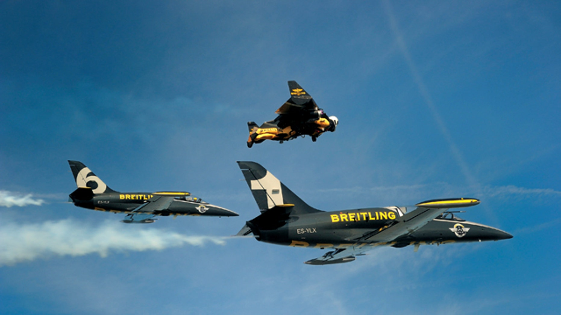 Jetman Yves Rossy flies in his custom wingsuit alogside a pair of Swiss air force jets.