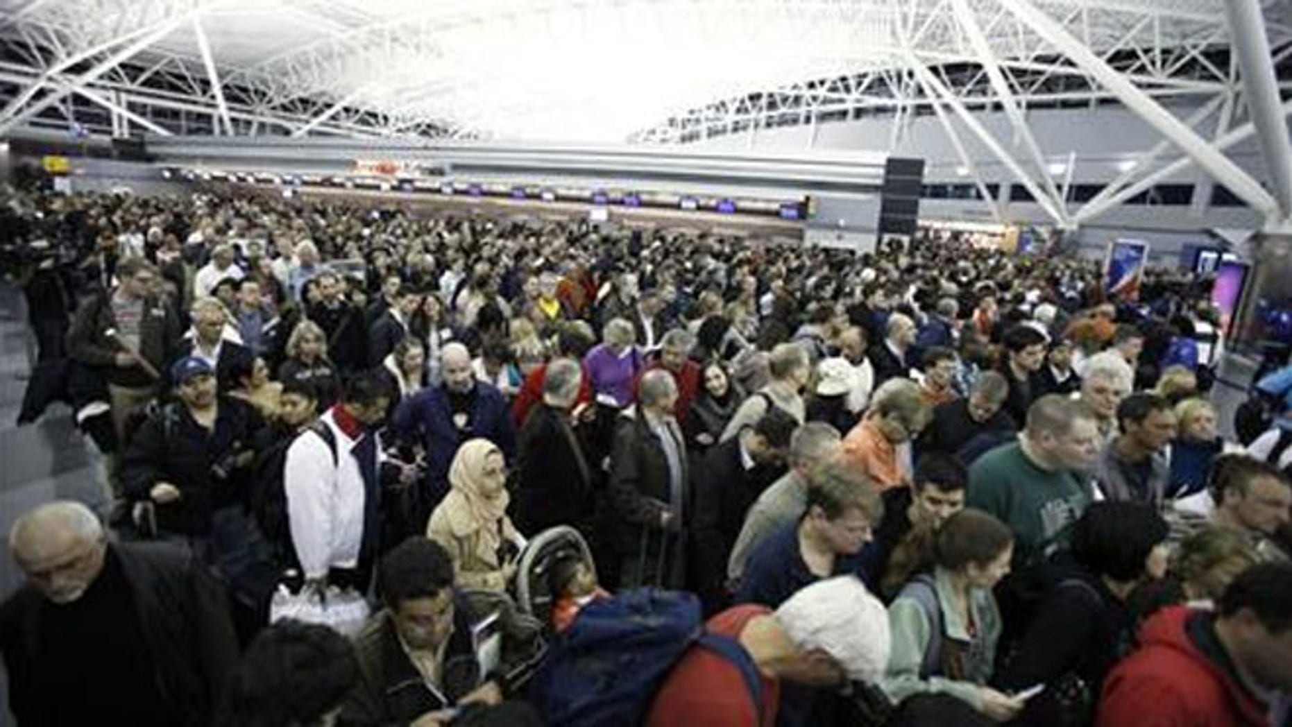 Airline passengers wait to re-enter Terminal 8 at the John F Kennedy.