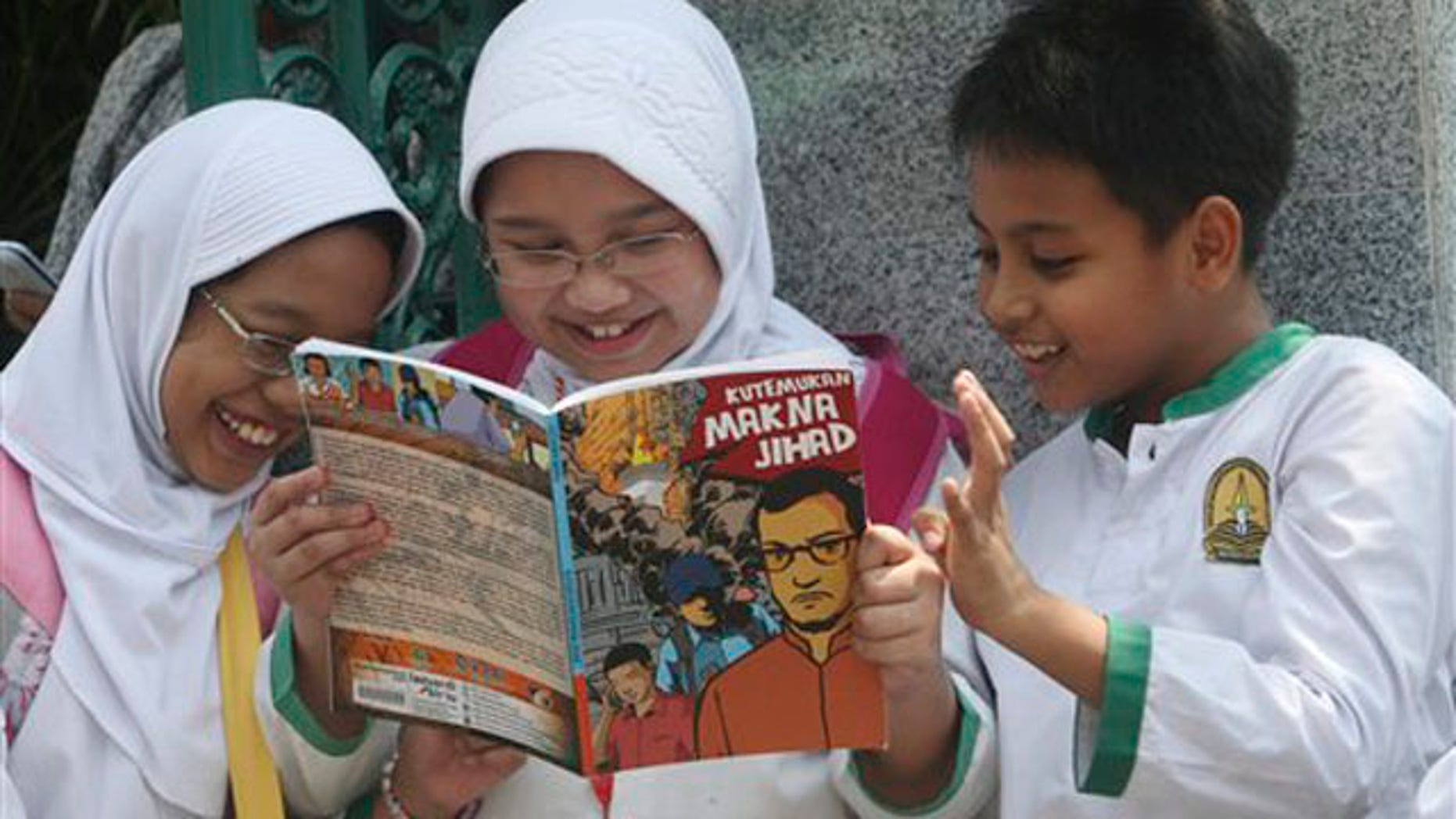 Students read a comic book with an anti-extremist theme at a primary school Friday, Sept. 9, 2011 in Jakarta, Indonesia.