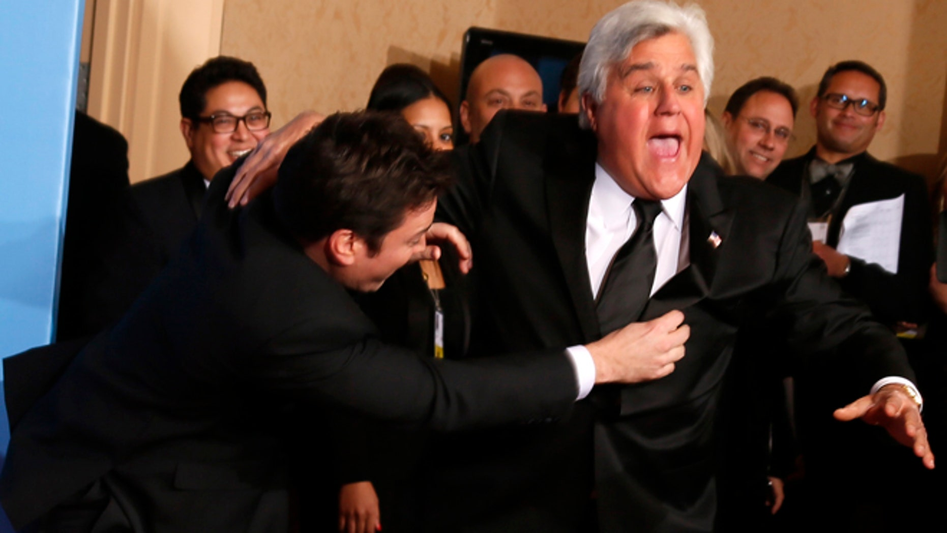 Late night talk show hosts Jimmy Fallon (L) and Jay Leno joke around backstage at the 70th annual Golden Globe Awards in Beverly Hills, California, January 13, 2013.