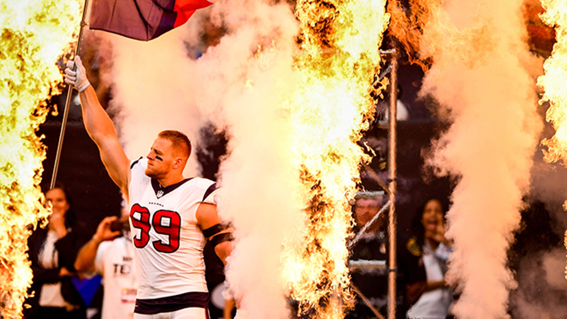 Houston Texans defensive end JJ Watt (99) waves a Texas state flag during player introductions before the game.