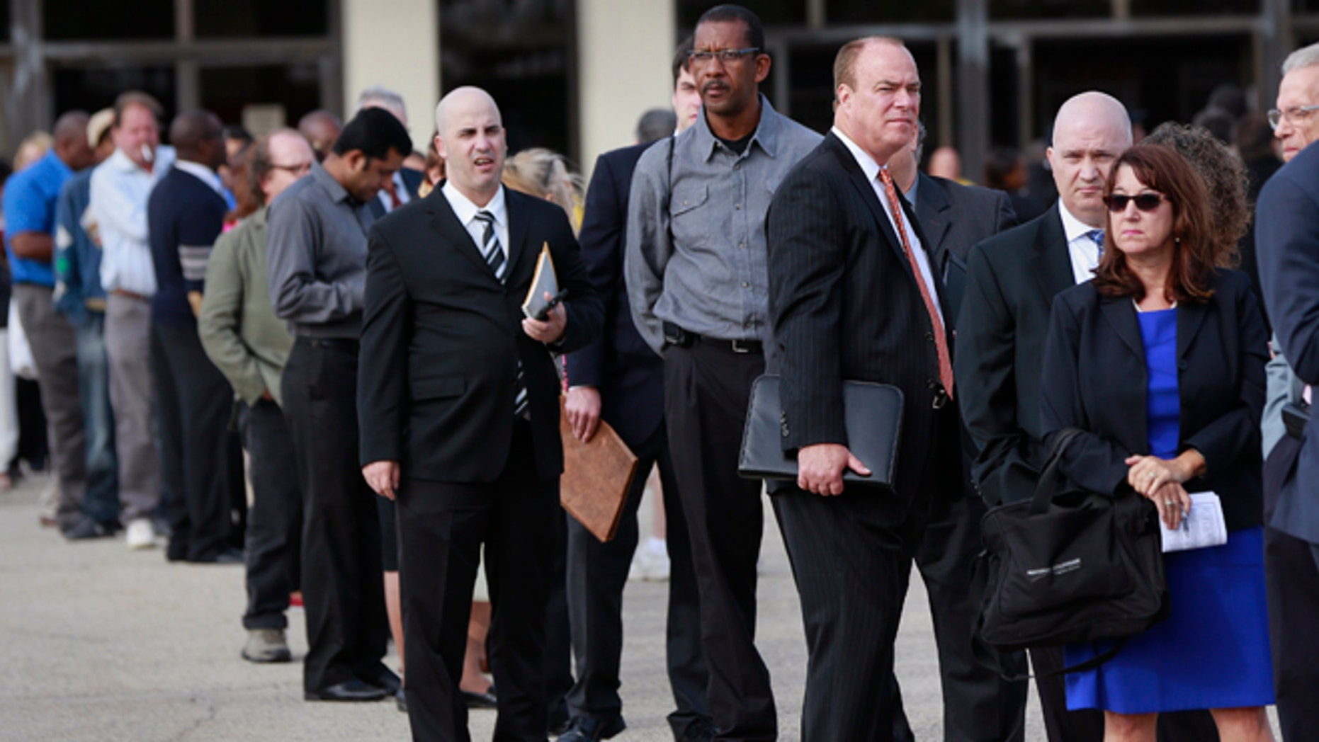In this Oct. 7, 2014 photo, people wait in line to enter the Nassau County Mega Job Fair at Nassau Veterans Memorial Coliseum in Uniondale, New York.