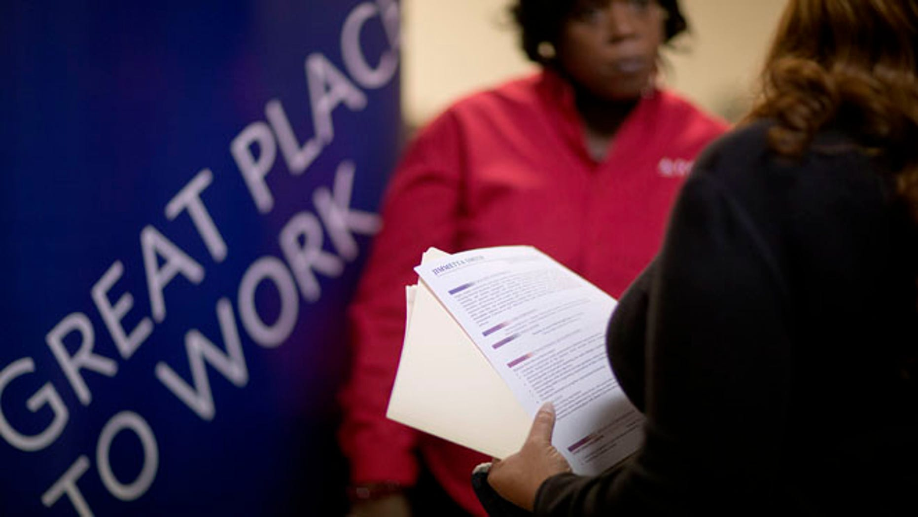 Nov. 14, 2013: A woman holds her resume while talking with a senior recruiter for Delta airlines at a job fair for veterans and family members in Marietta, Ga.